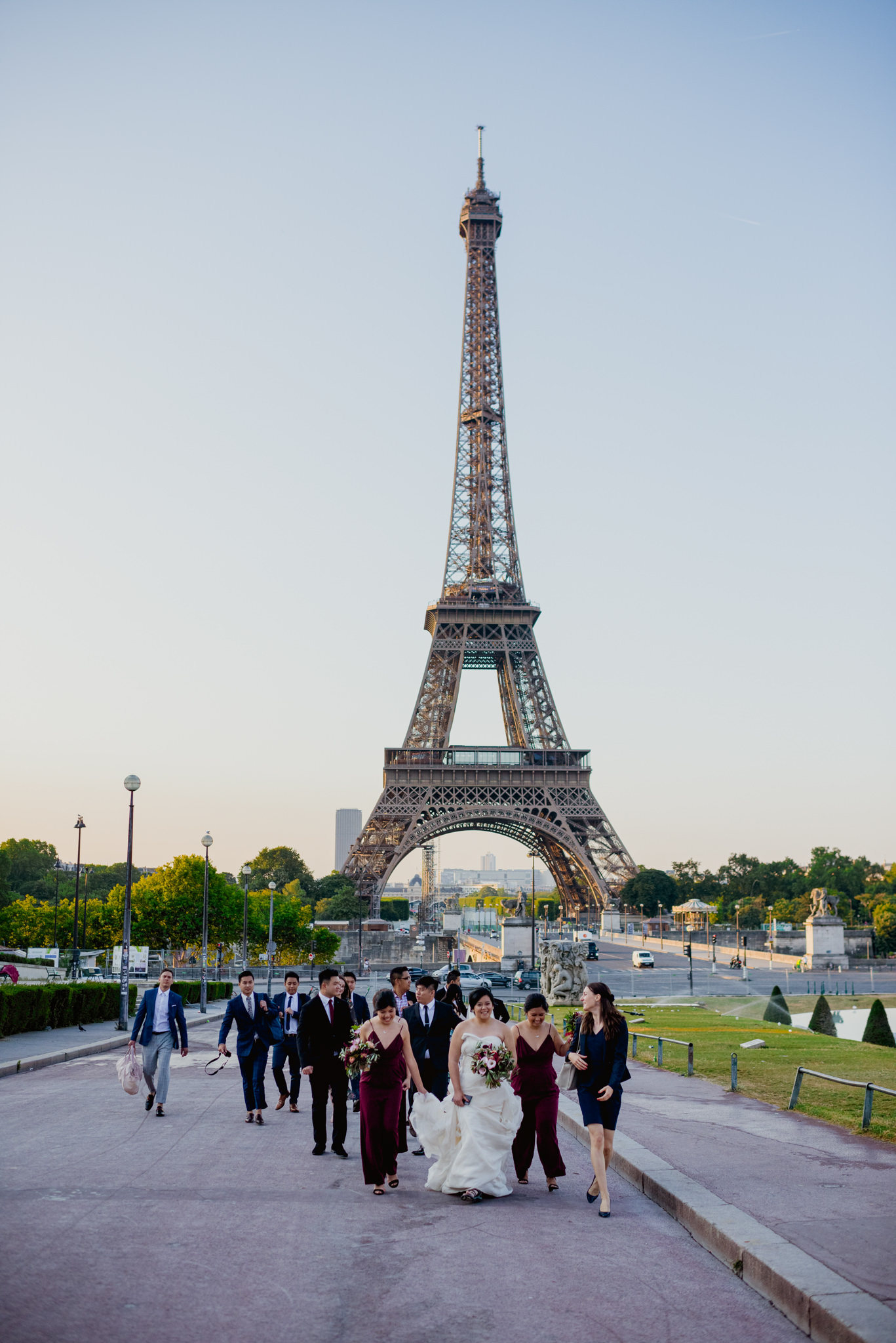 A bridal party walks up a hill with the Eiffel Tower behind them.