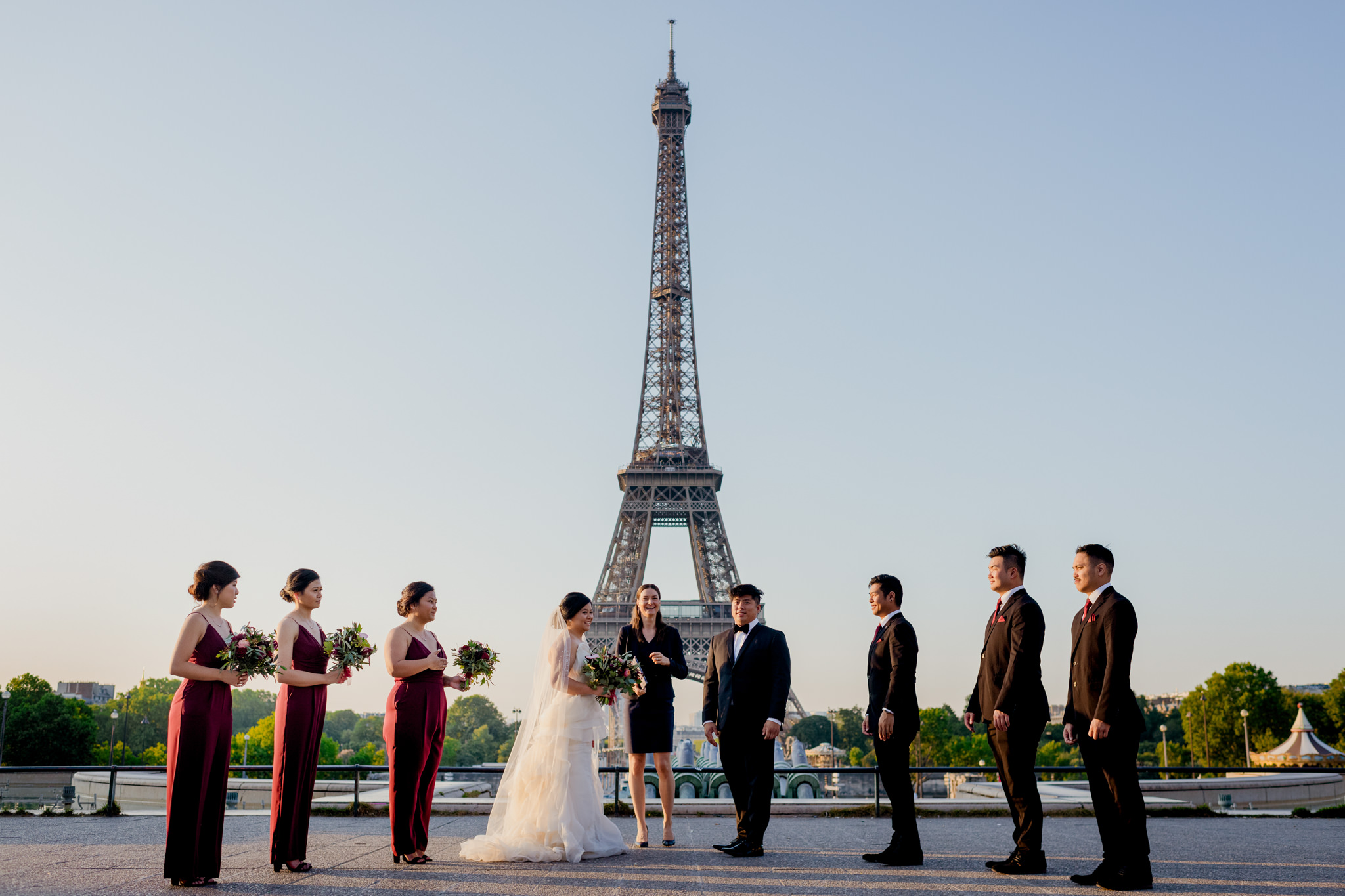 A bridal party lines up for a wedding in front of the Eiffel Tower.