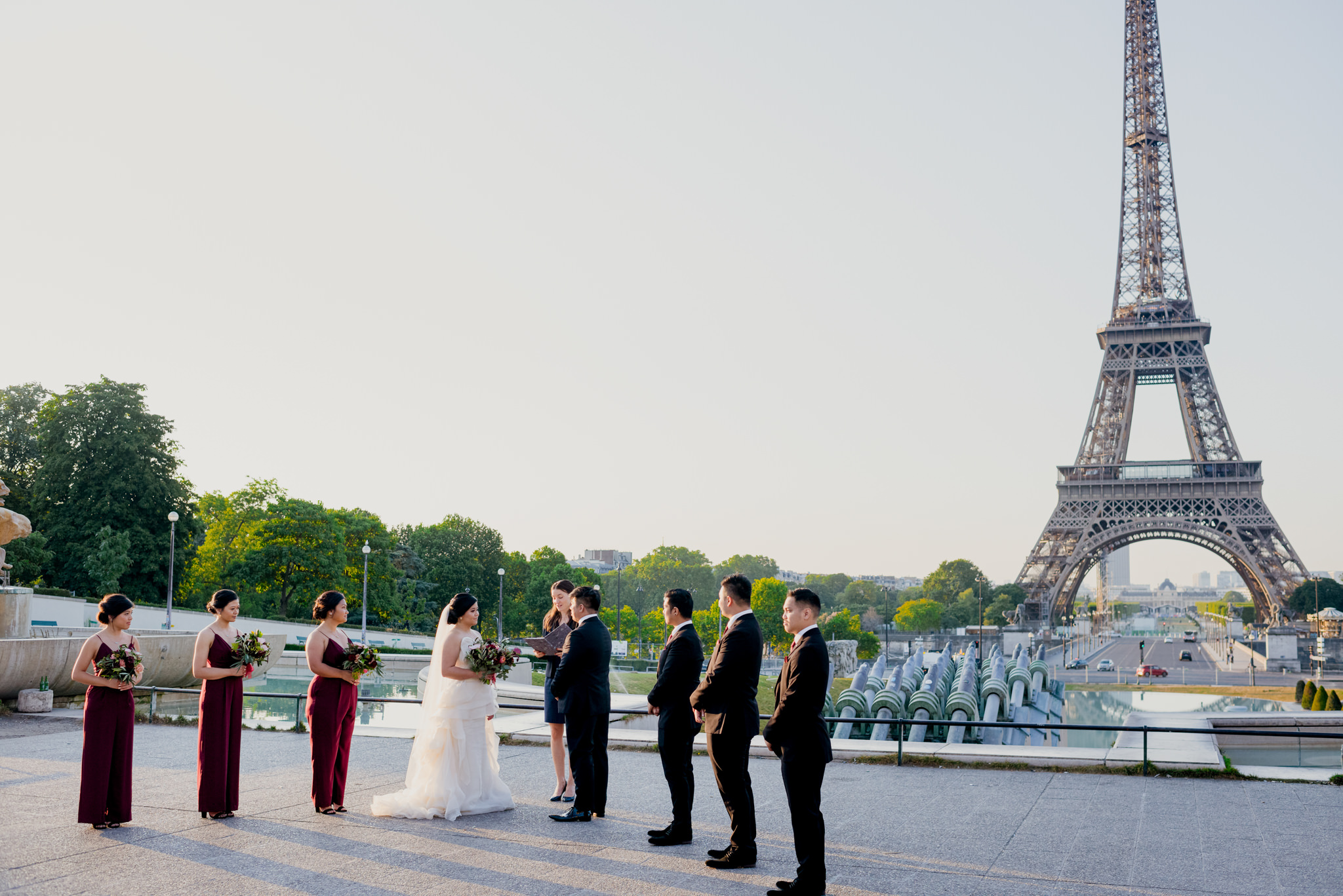 A bridal party lines up for a wedding with the Eiffel Tower in the background.