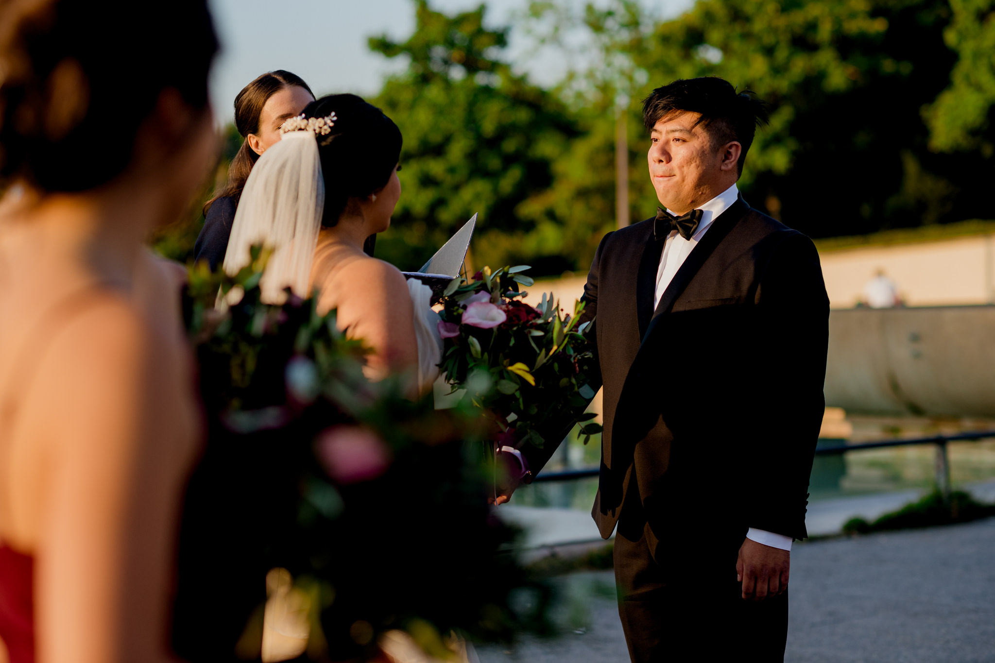 A groom bites his lip and holds back tears at his wedding.
