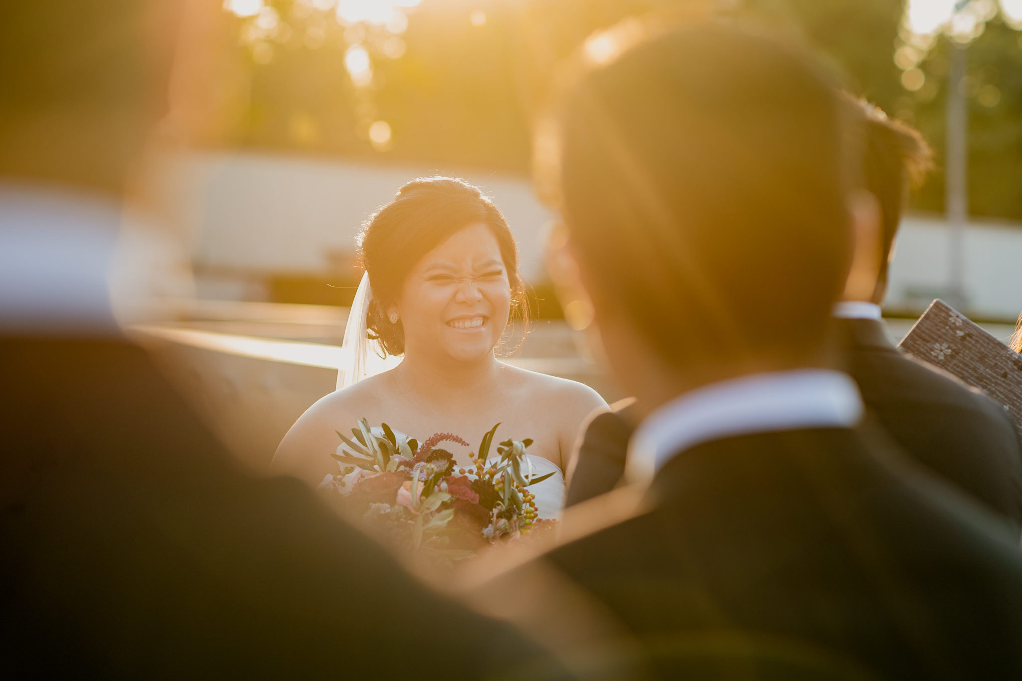 An asian bride laughs as the sun shines on her head.
