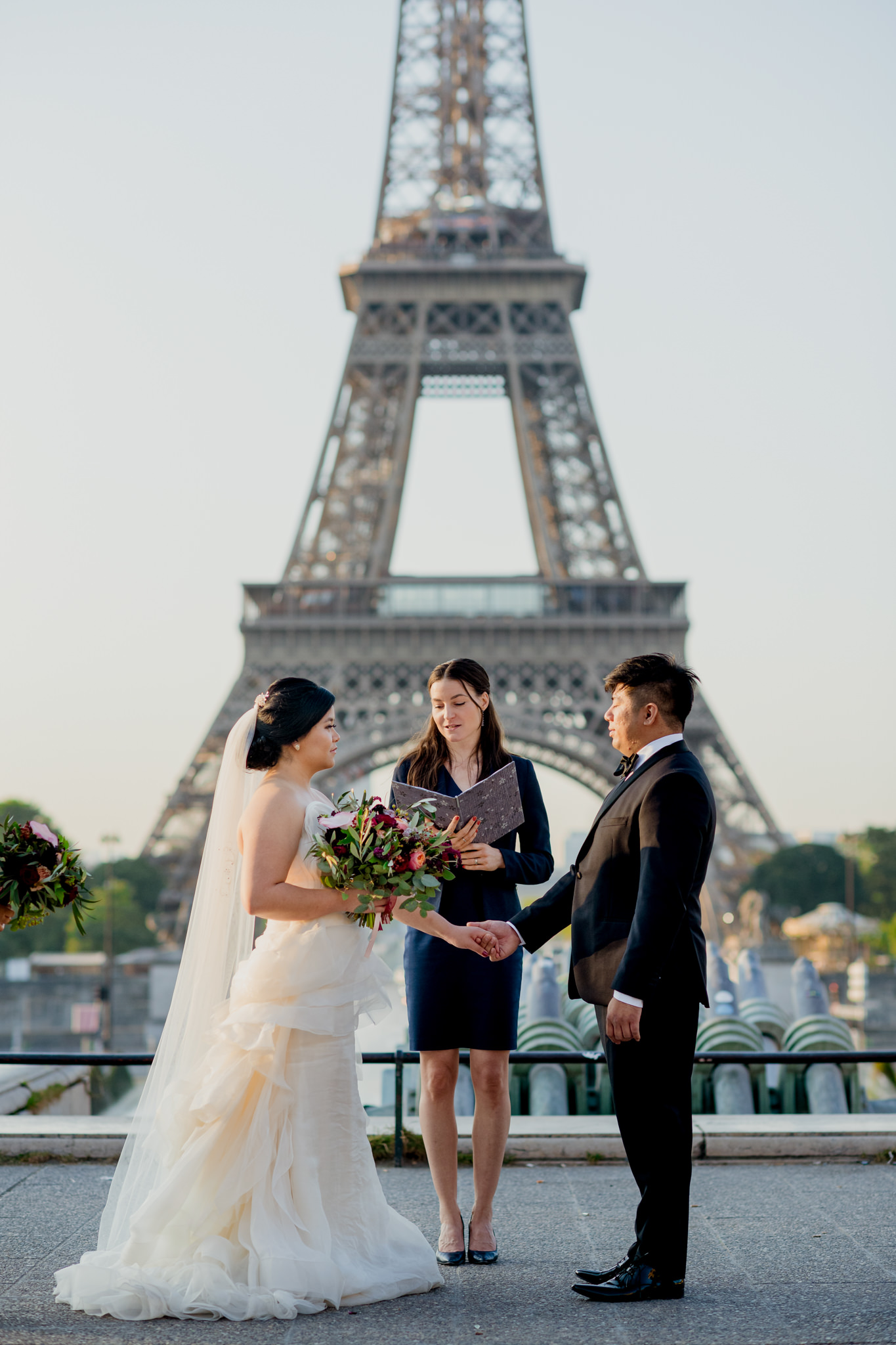 A bride and groom hold hands in front of the Eiffel Tower as their celebrant reads to them.