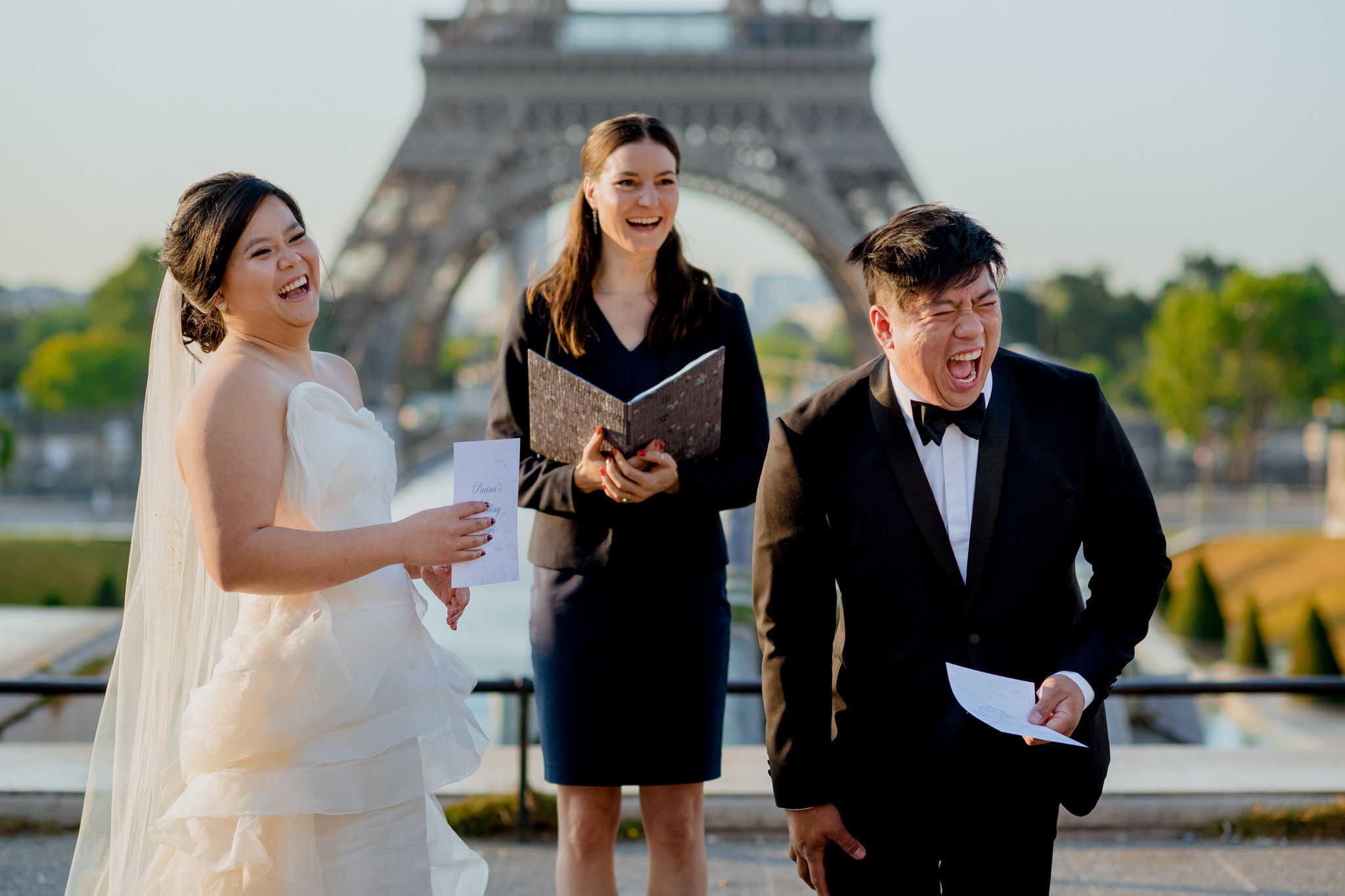 A groom laughs hysterically as her recites his wedding vows in Paris.