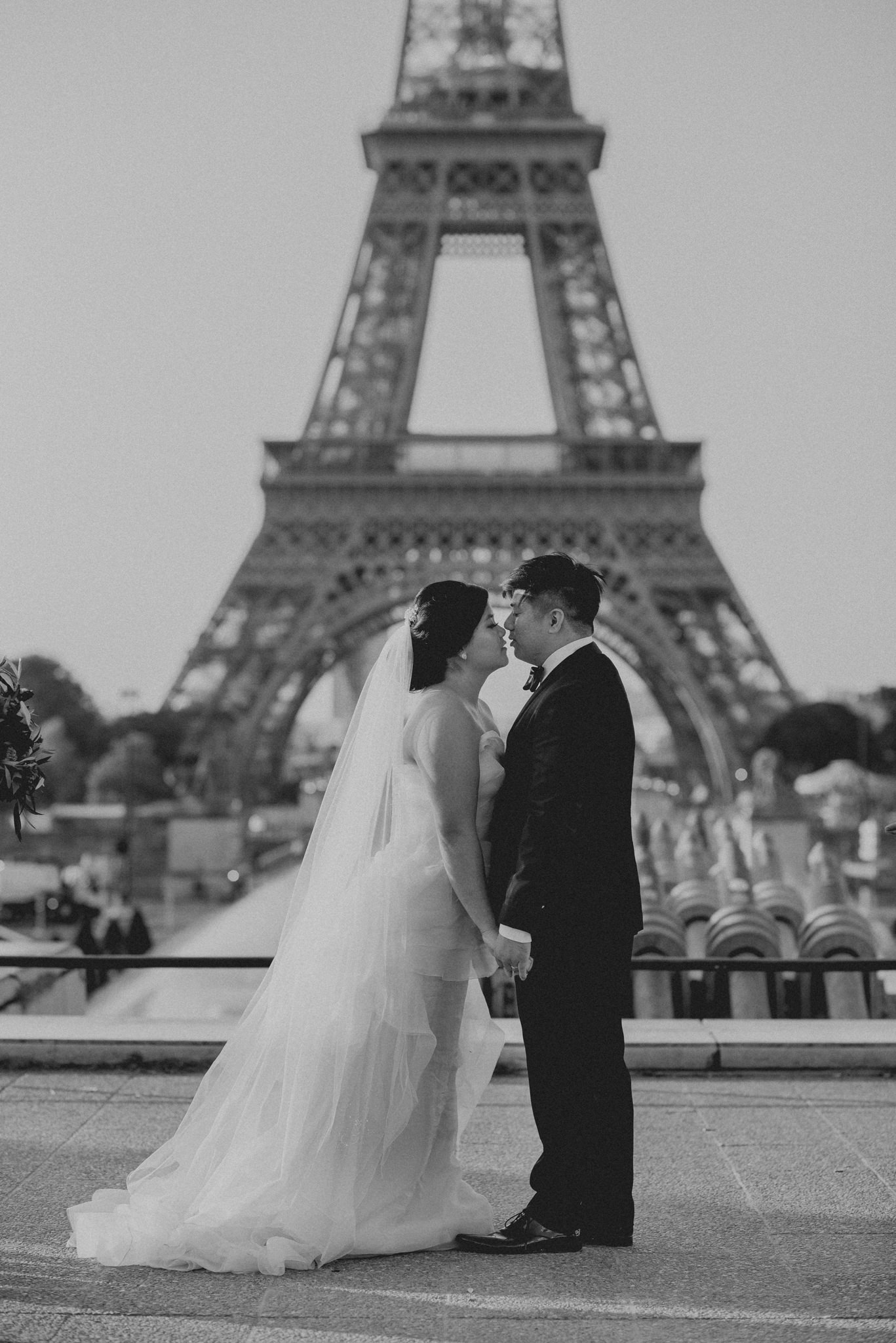 Asian bride and groom kiss in front of the Eiffel Tower.