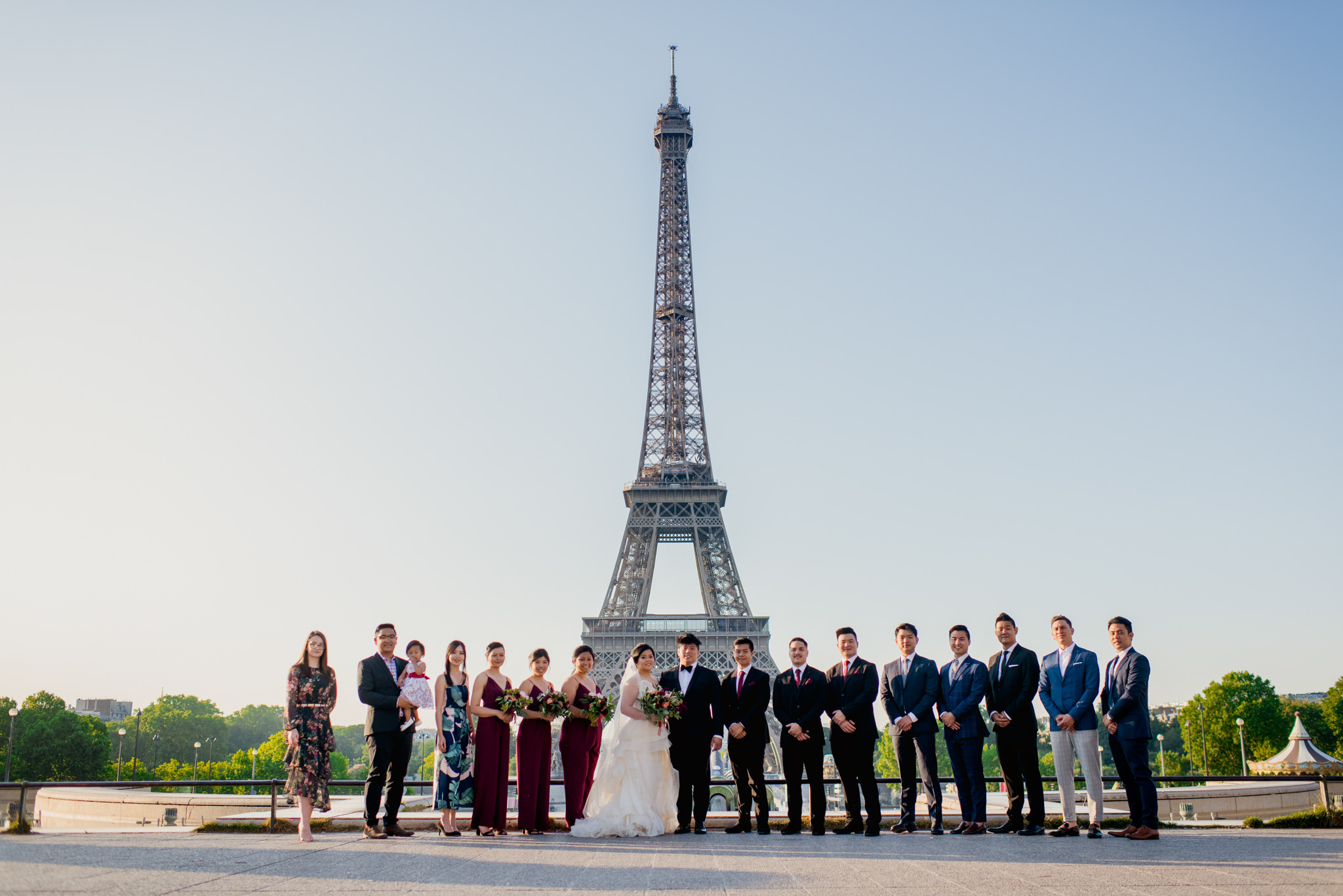 Wedding guests line up in front of the Eiffel Tower.