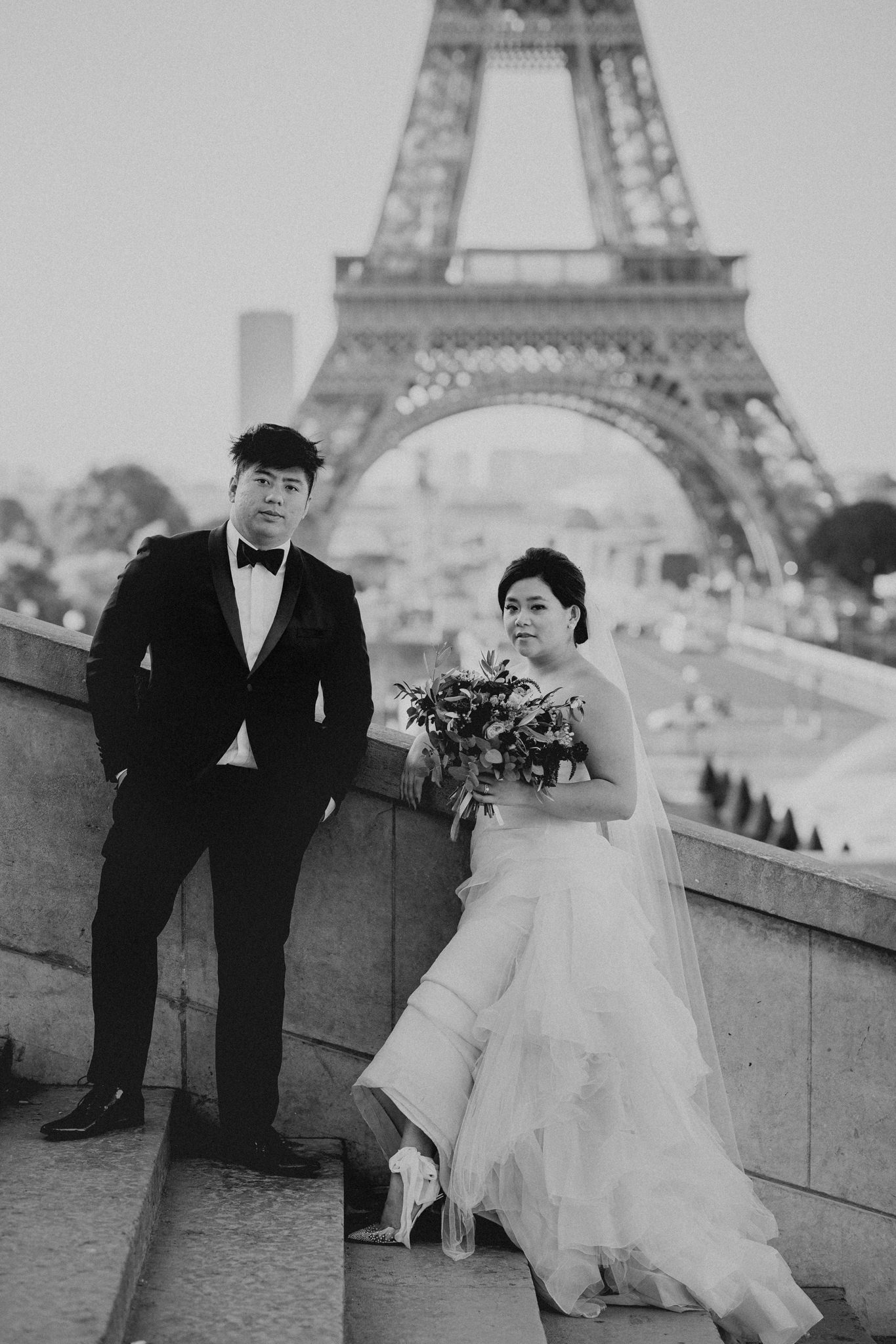 Asian bride and groom stand on steps in front of the Eiffel Tower.