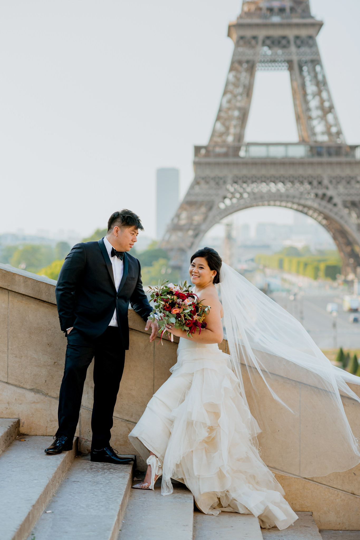 Asian bride and groom stand on steps and laugh in front of the Eiffel Tower.