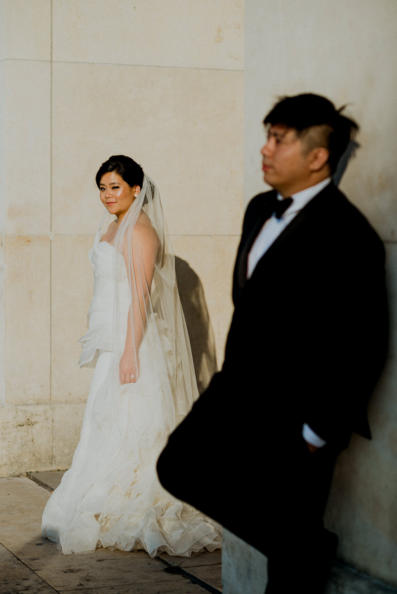 Bride poses in background as groom is out of focus in foreground