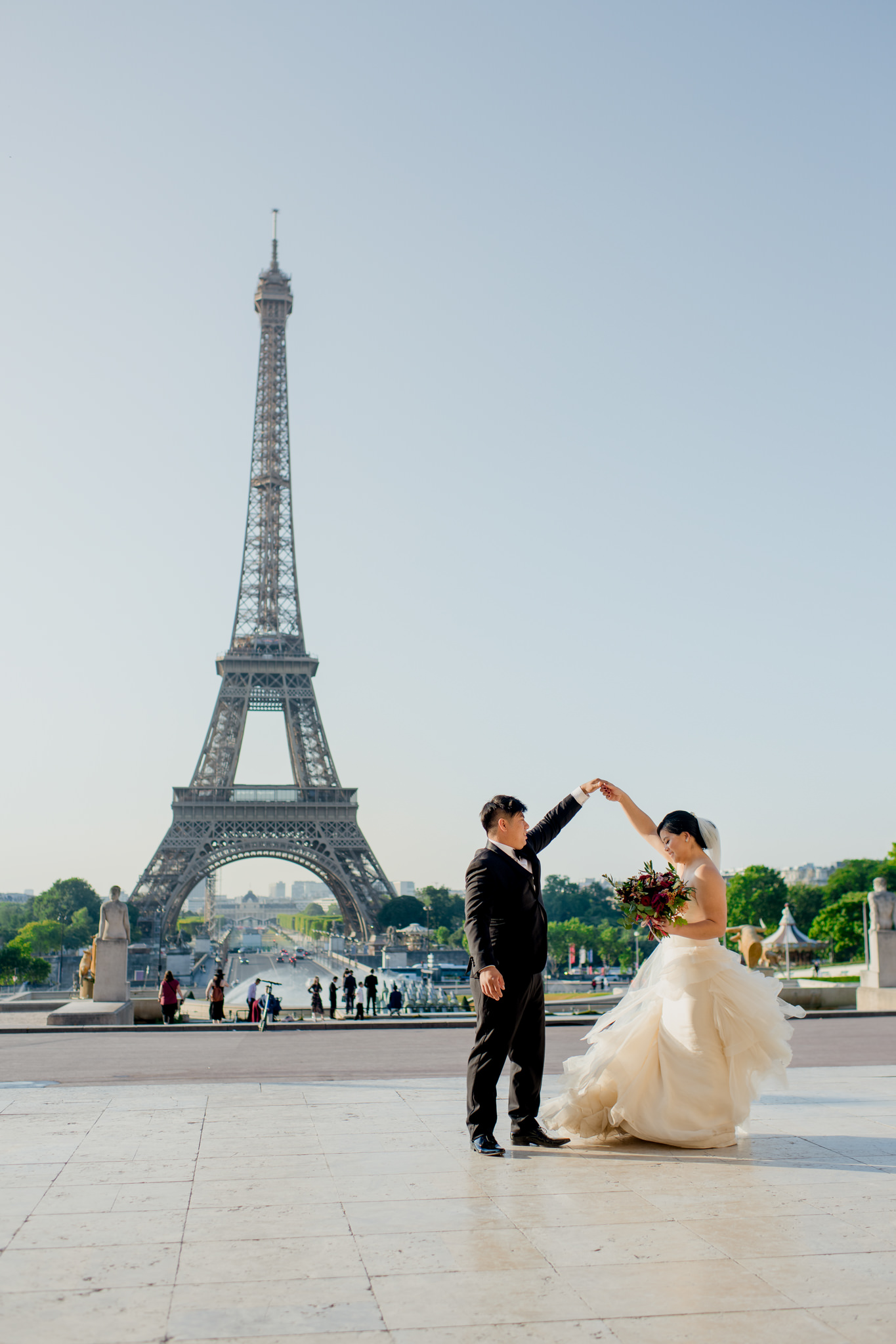 Bride and groom dance with the Eiffel Tower in the background.