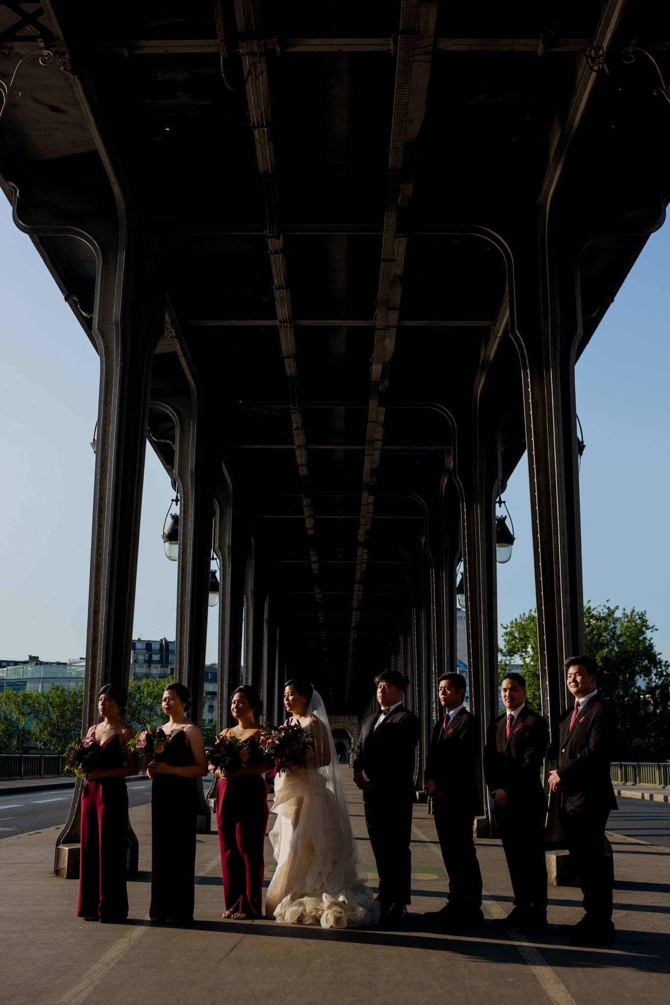 Bridal party line up in shadows on the Bir-Hakeim bride, Paris