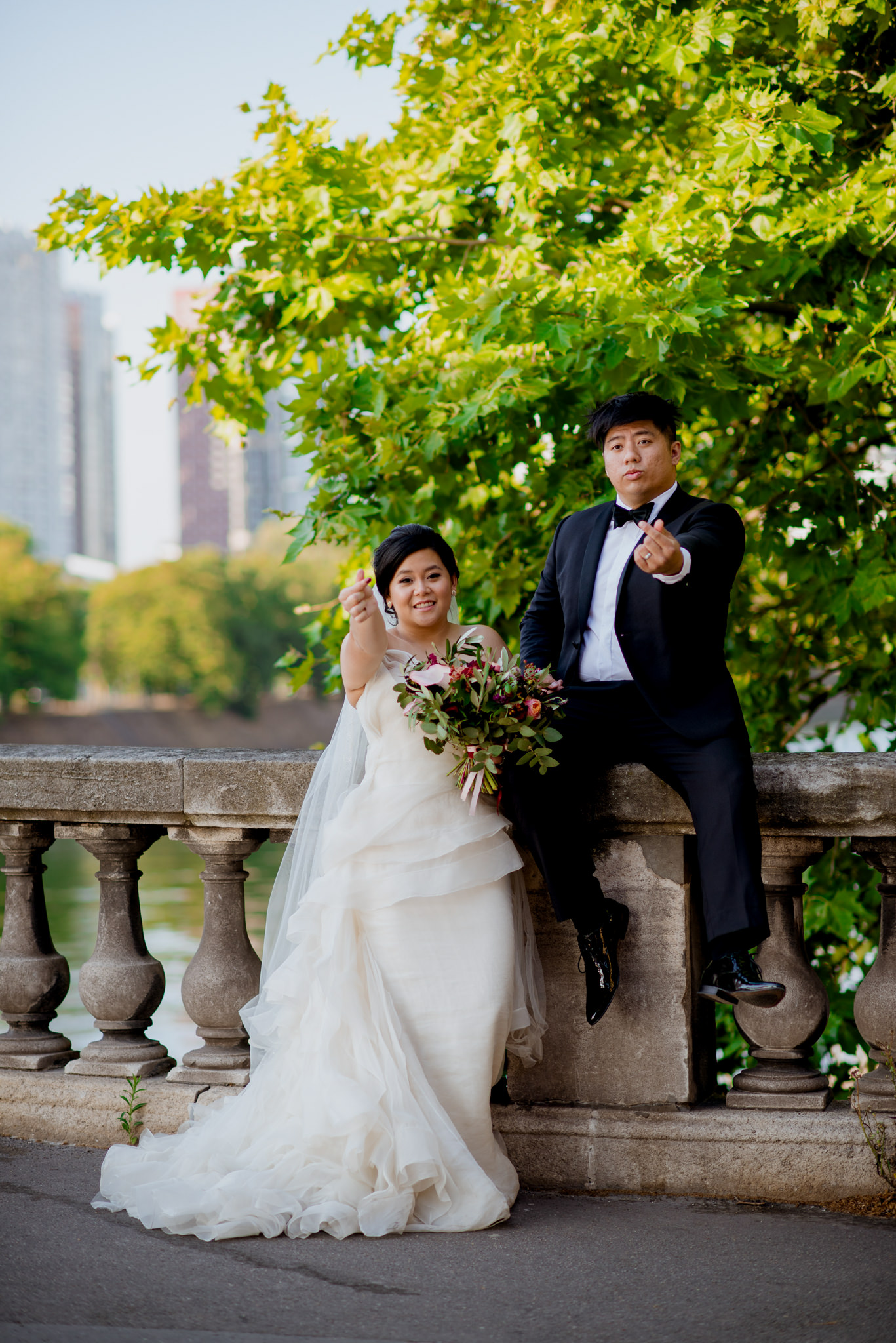 Asian bride and groom pose on bridge in Paris.