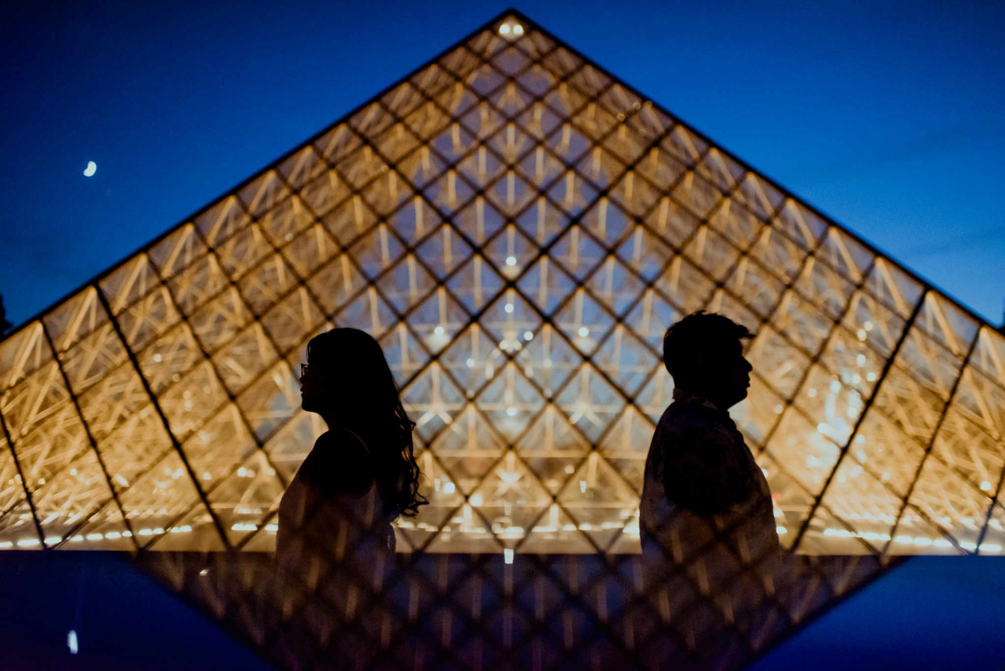 Silhouette of a man and a woman facing away from each other in front of the Louvre Pyramids.