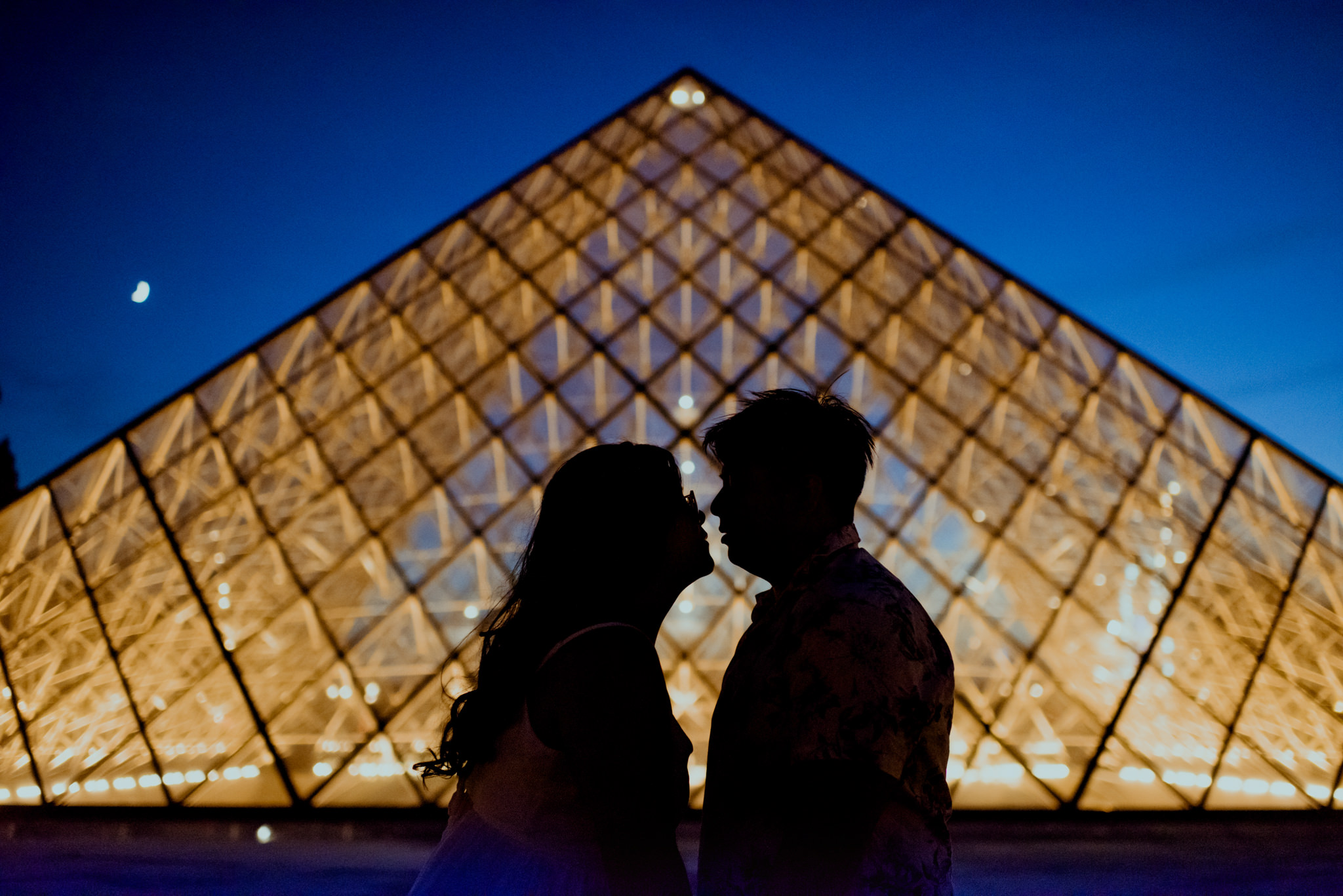 Silhouette of a man and a woman facing each other in front of the Louvre Pyramids.