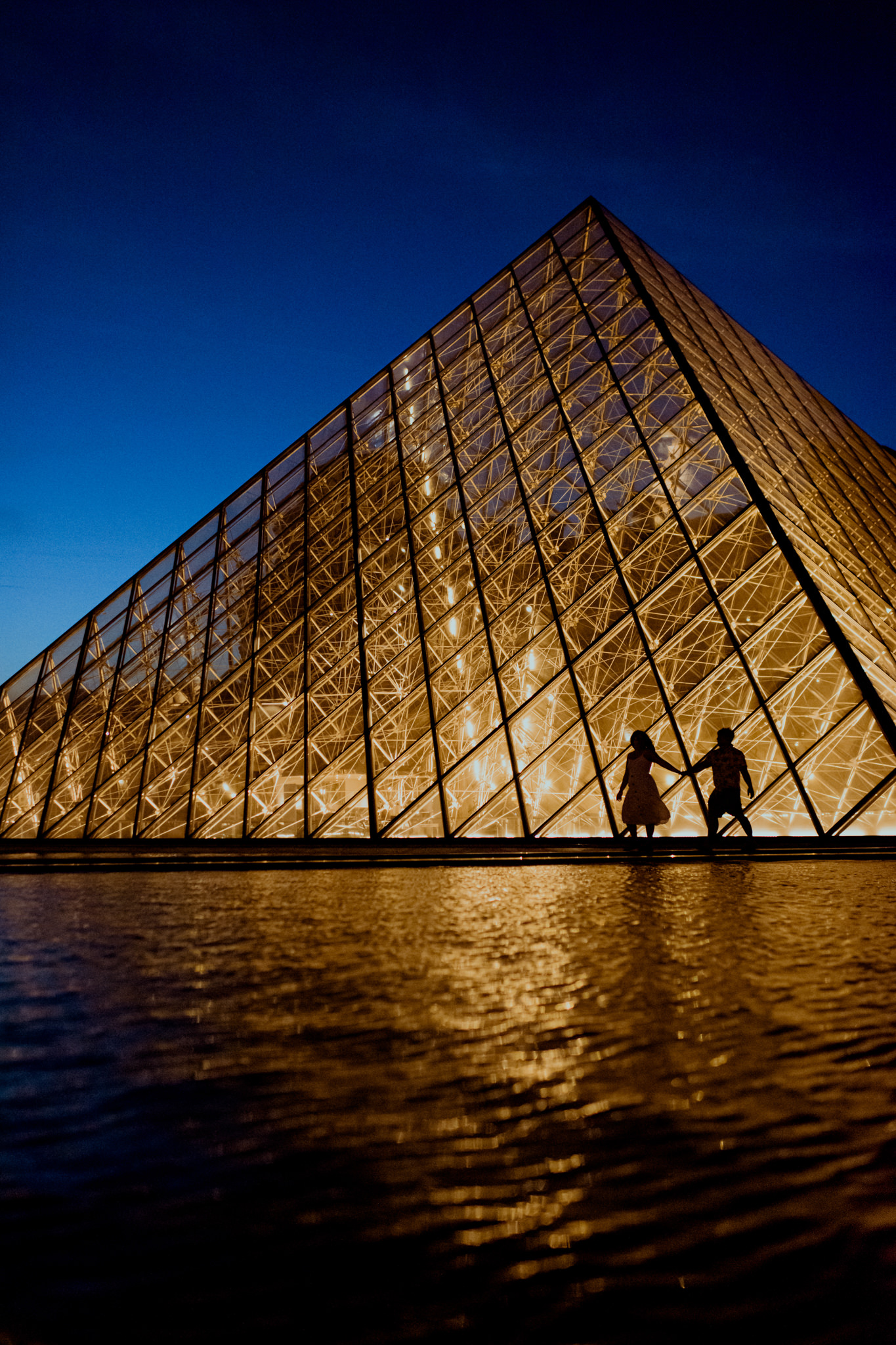 Silhouette of a man and a woman holding hands and walking in front of the Louvre Pyramids.