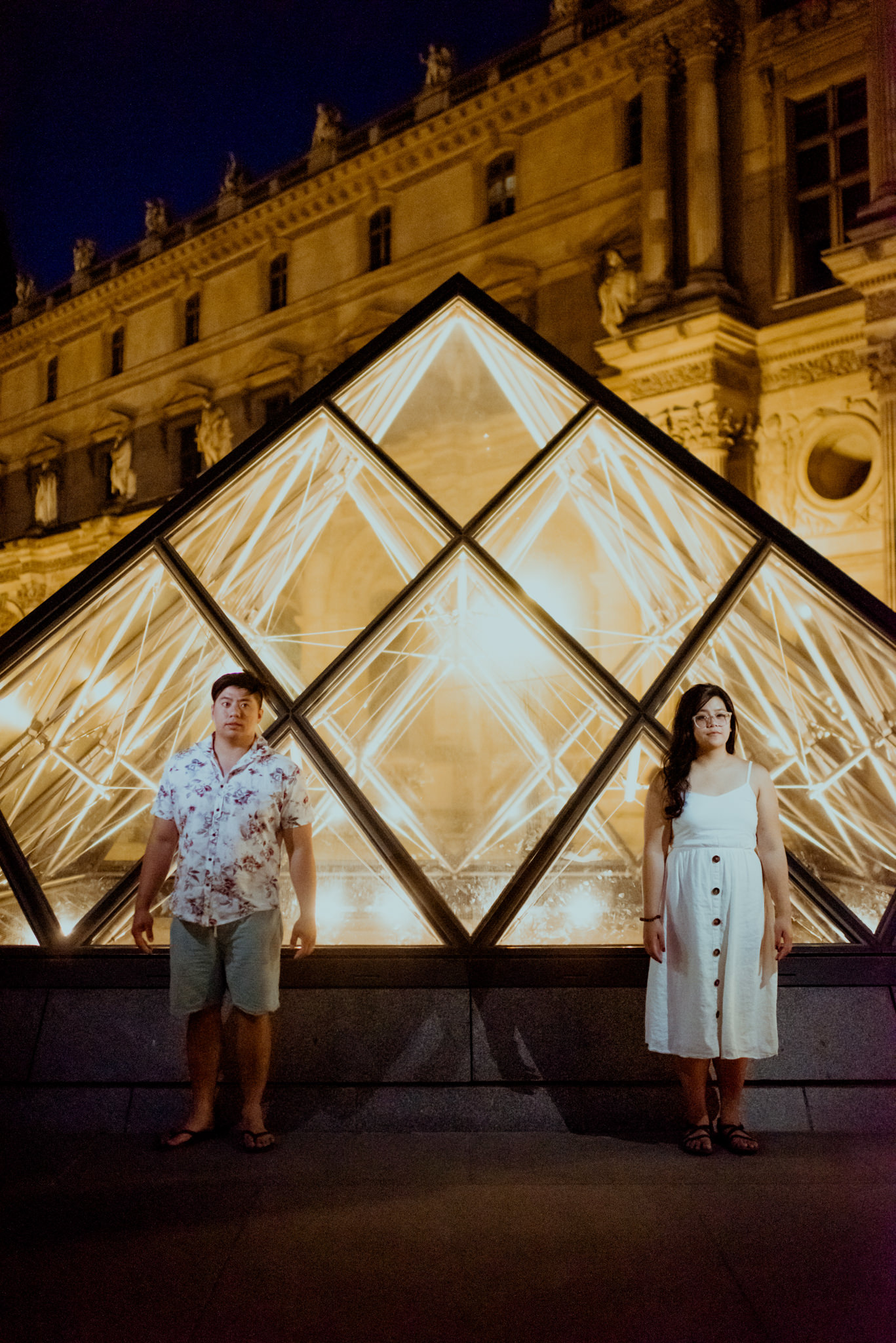 Asian man and woman stand in front of the Louvre Pyramids.