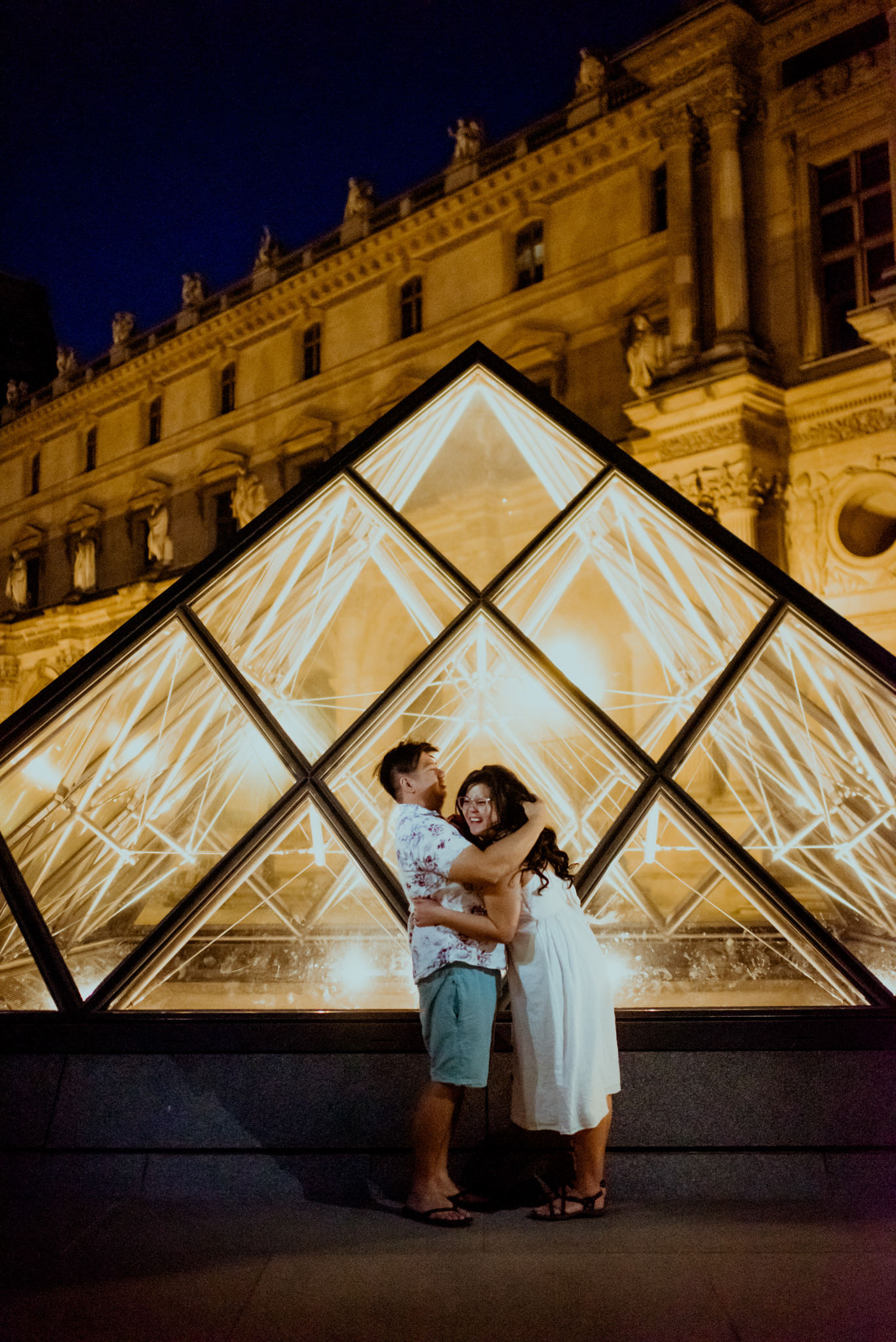 Asian man and woman hug in front of the Louvre Pyramids.