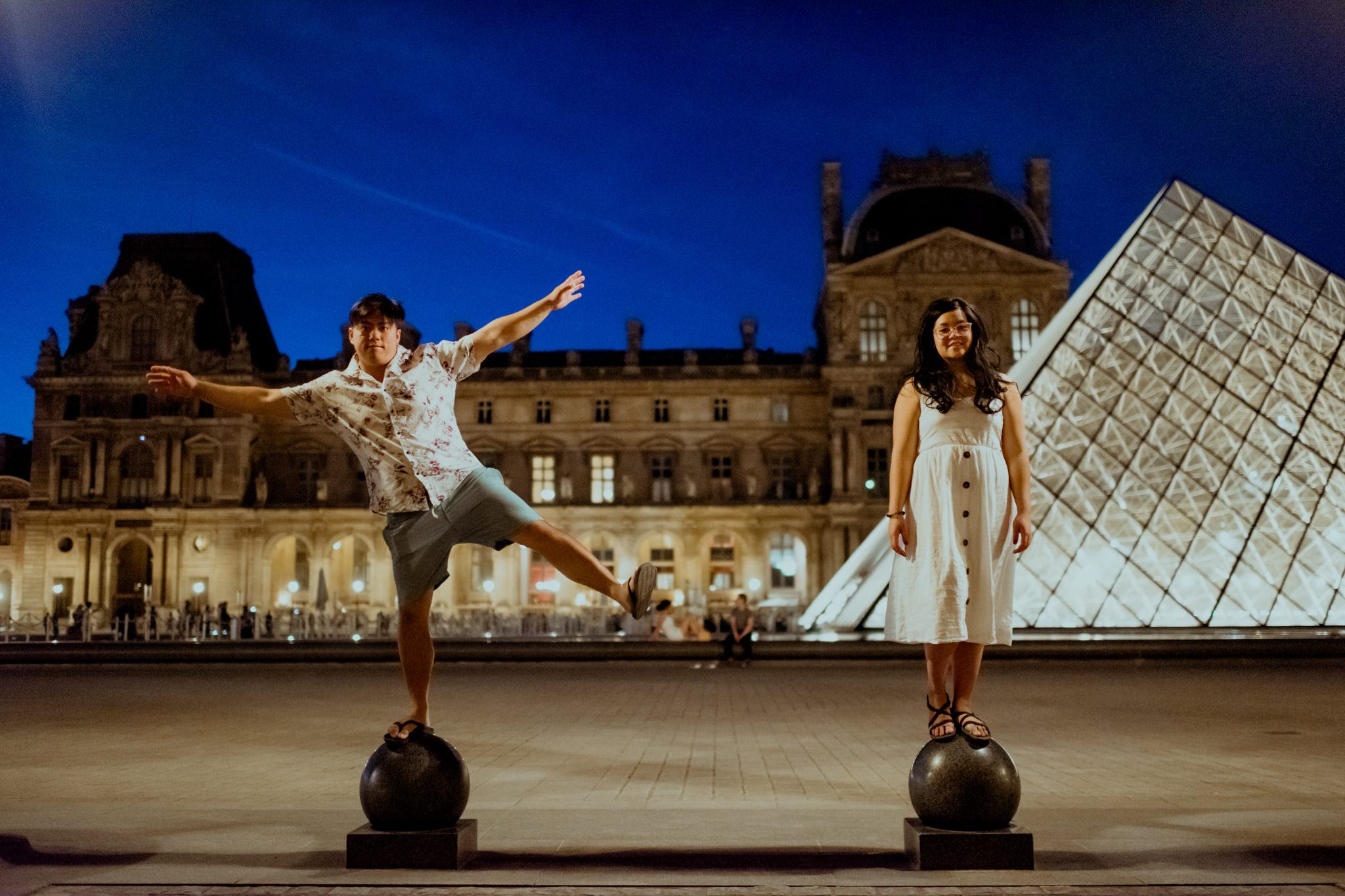 Asian couple try to balance on round balls at the Louvre, Paris.