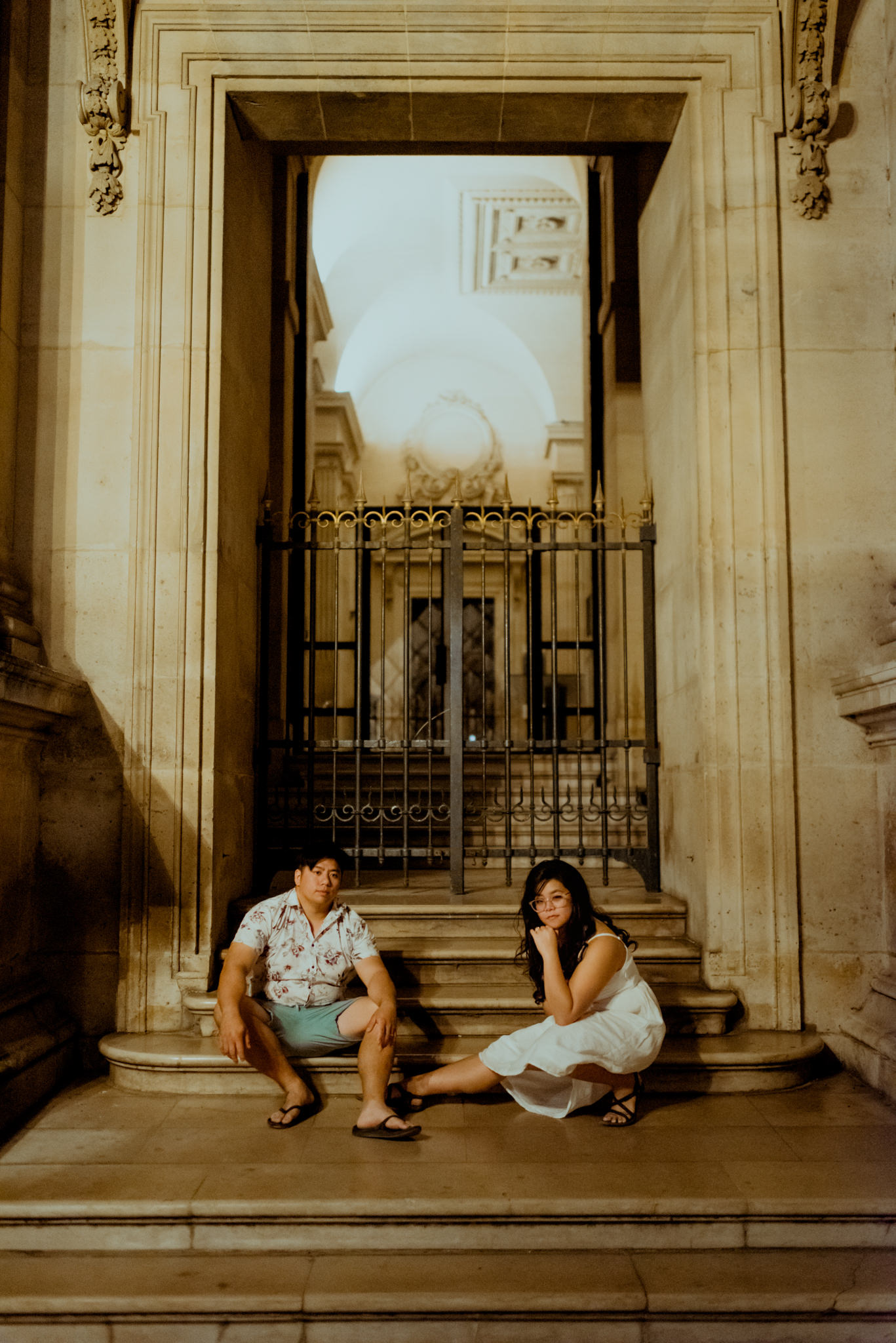 Asian couple pose seriously on the steps at the Louvre, Paris.