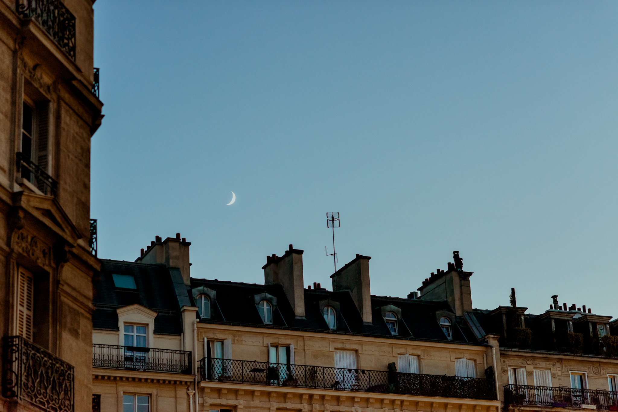 The moon rising over the walls of the Louvre, Paris.