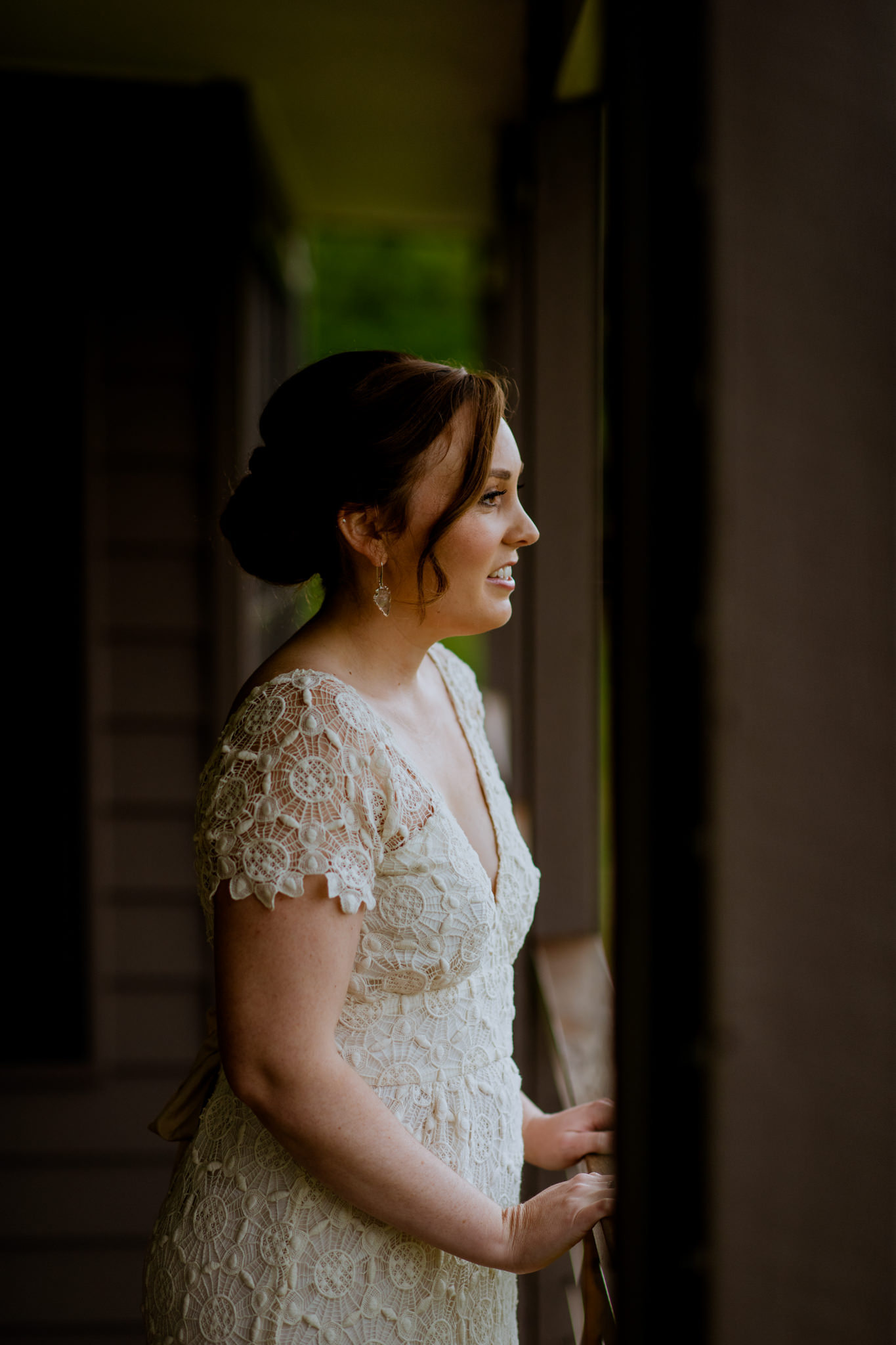Anxious bride stands on balcony and looks right