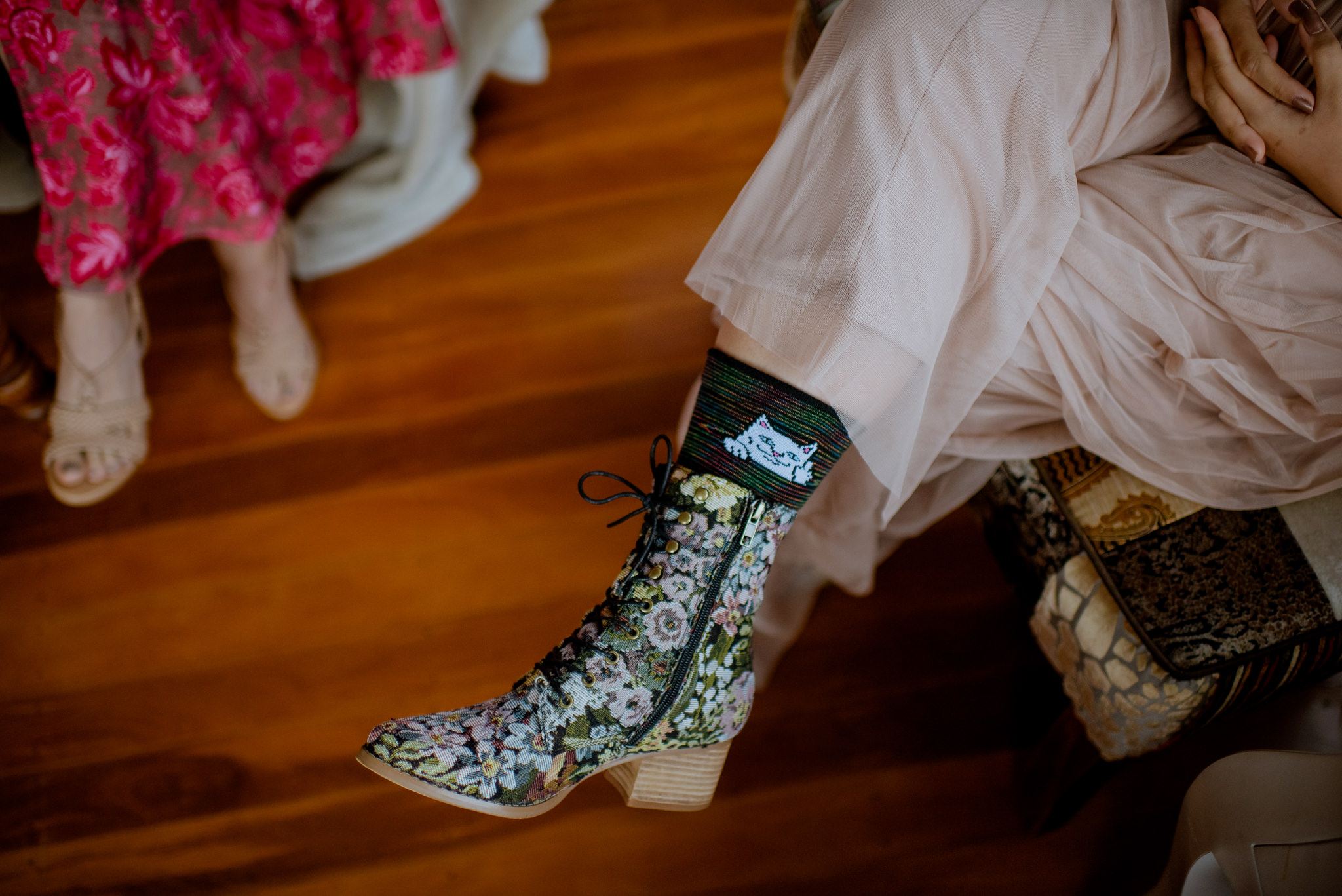 Closeup of flowery print boots and cat socks on someone's leg