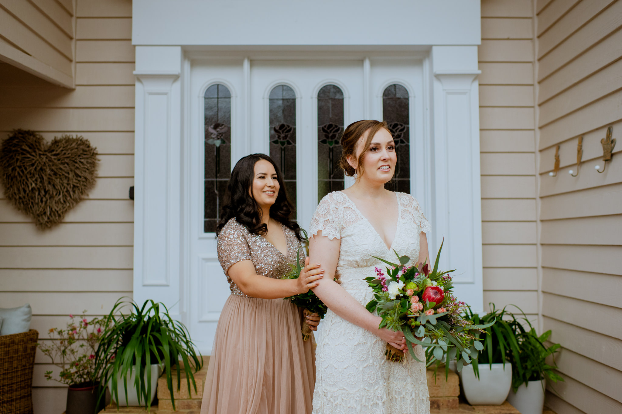 Same sex couple's first look before their wedding in front of white doors