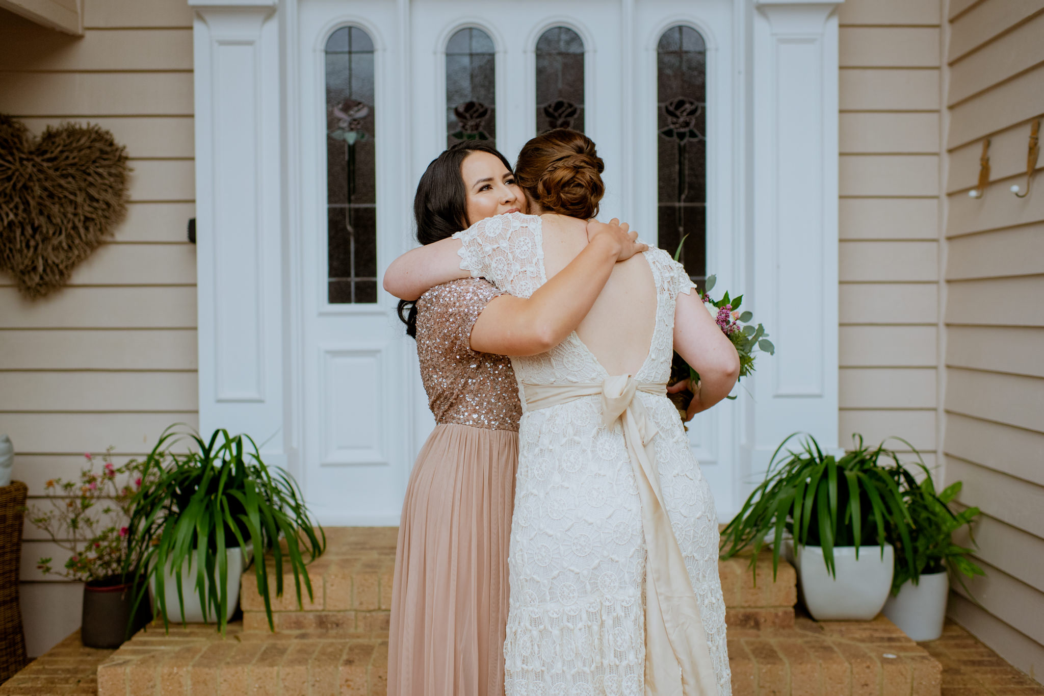 Same sex couple embrace in front of white doors