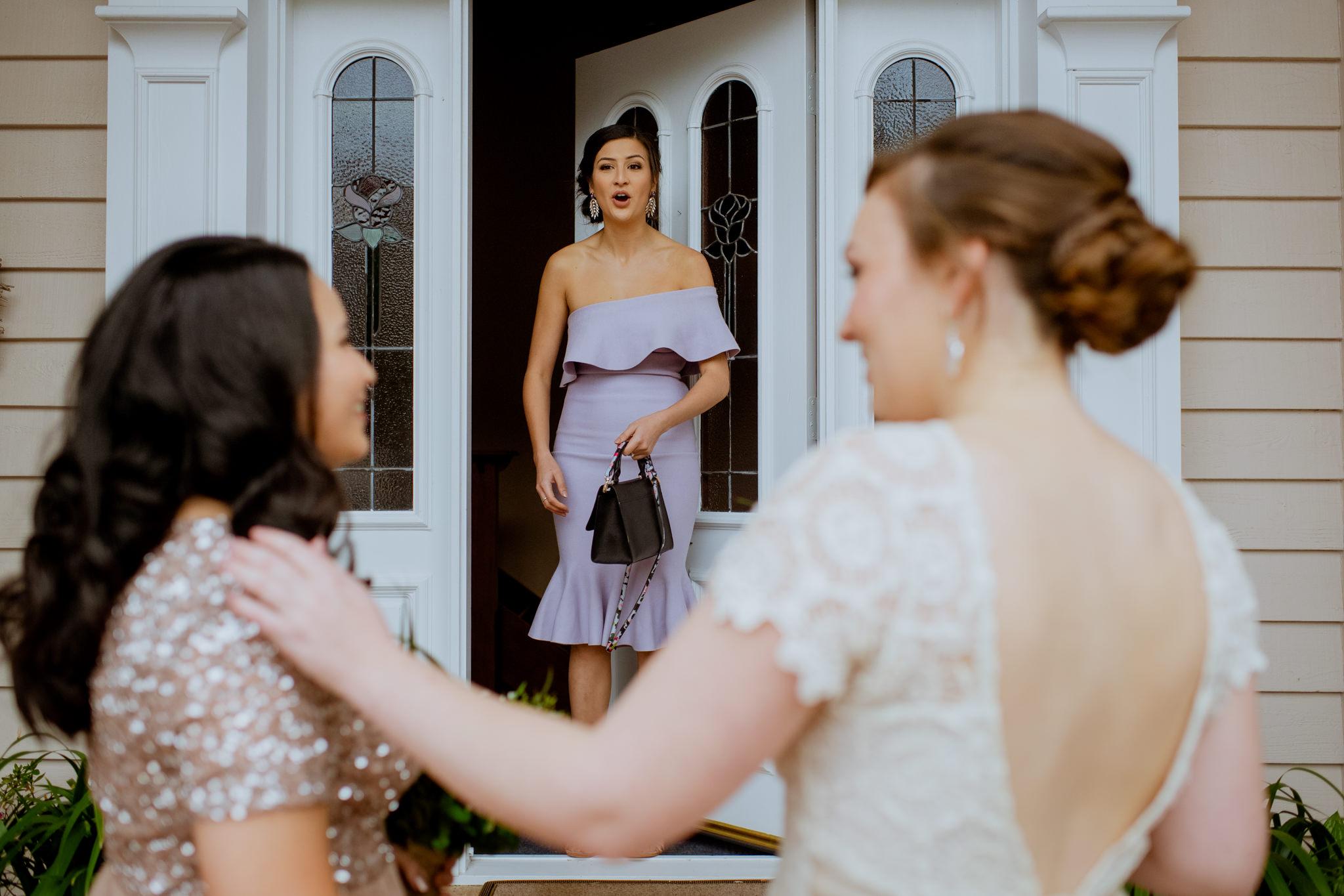 Girl in purple dress looks shocked in doorway in front of same sex couple