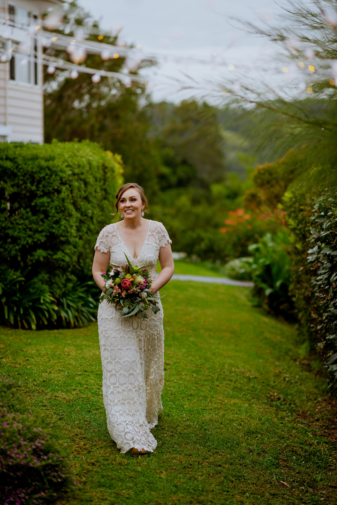 Bride smiles and walks on grass next to bushes