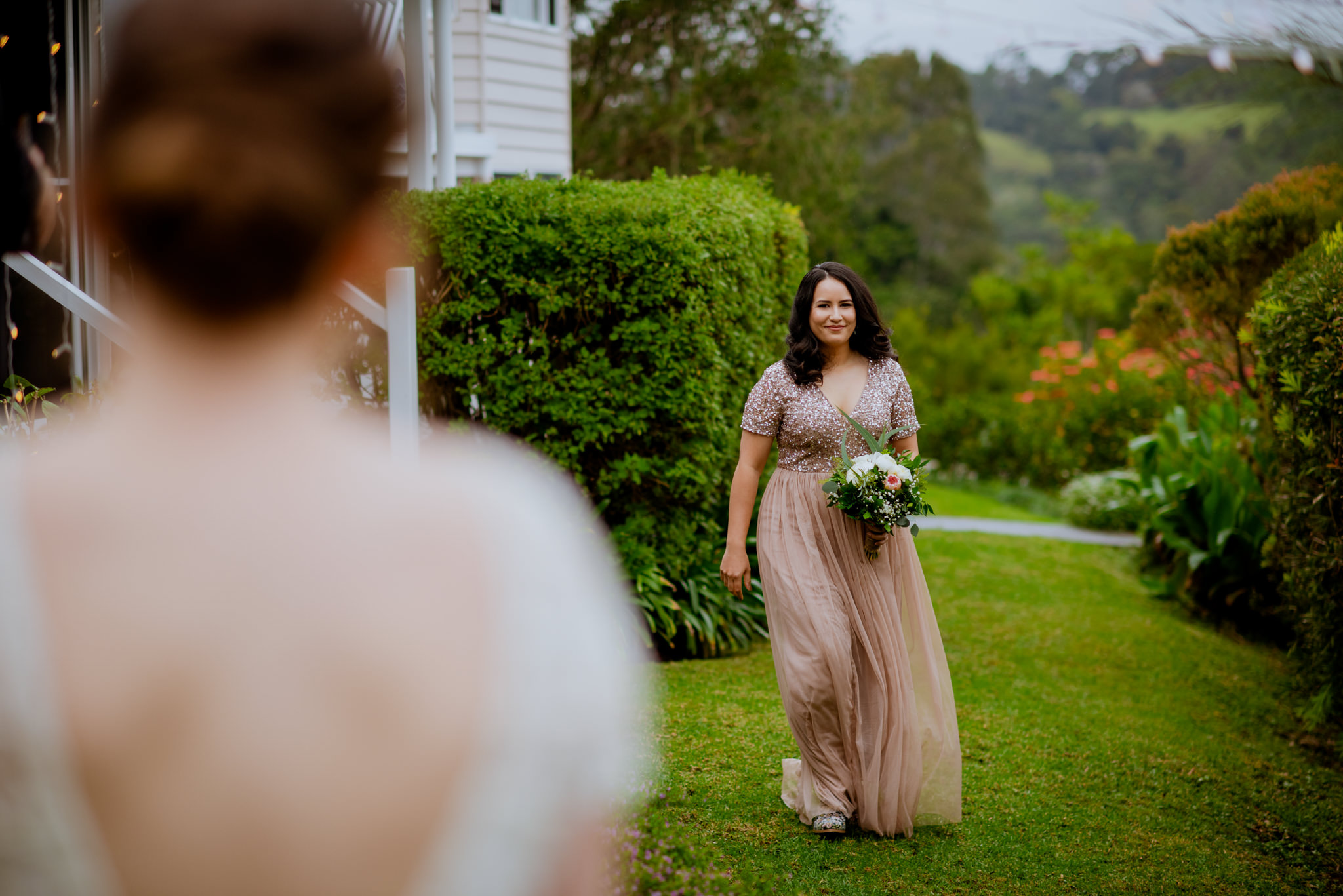 Bride smiles and walks on grass next to bushes with another bride out of focus in foreground