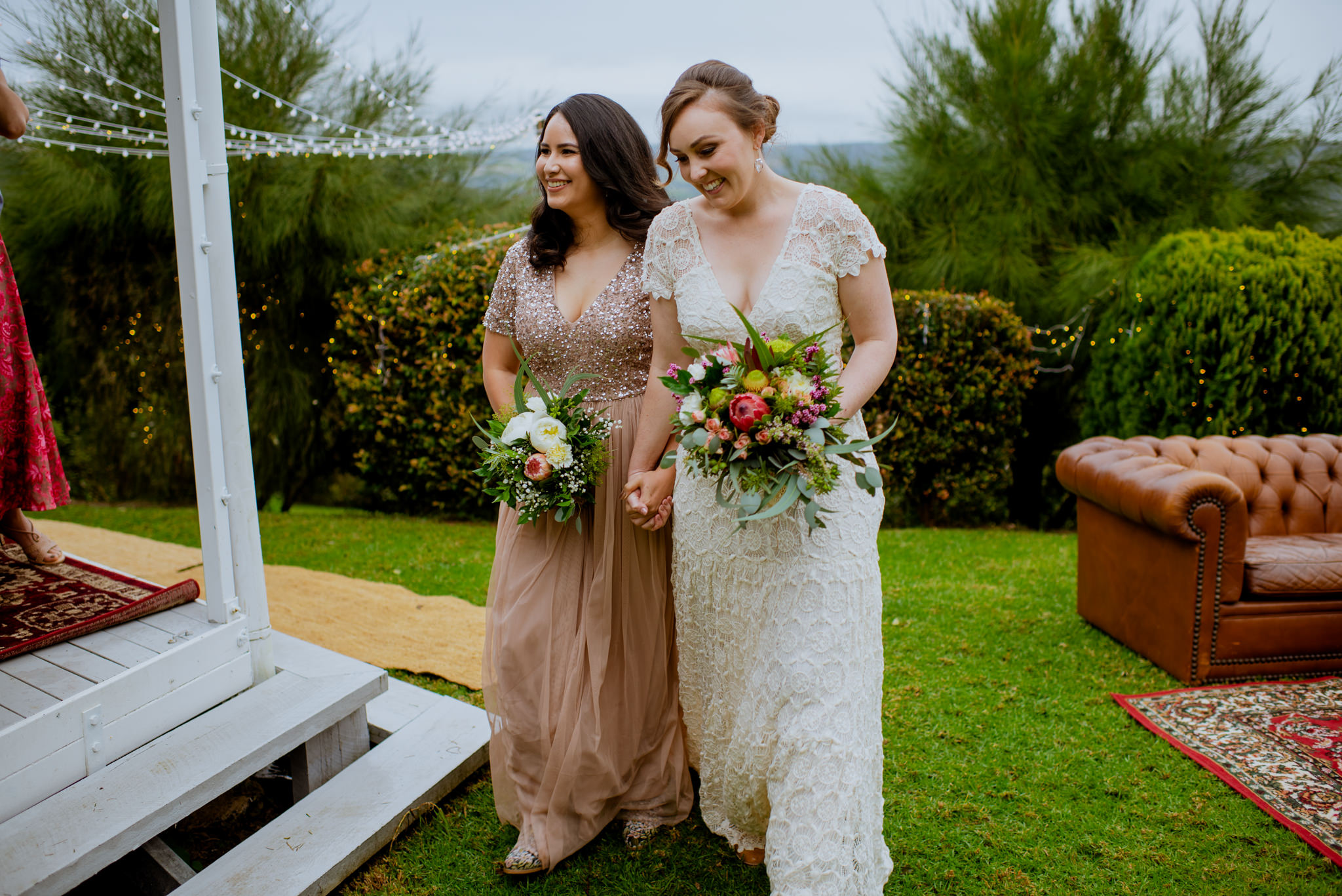 Two brides walk hand-in-hand on grass next to a verandah