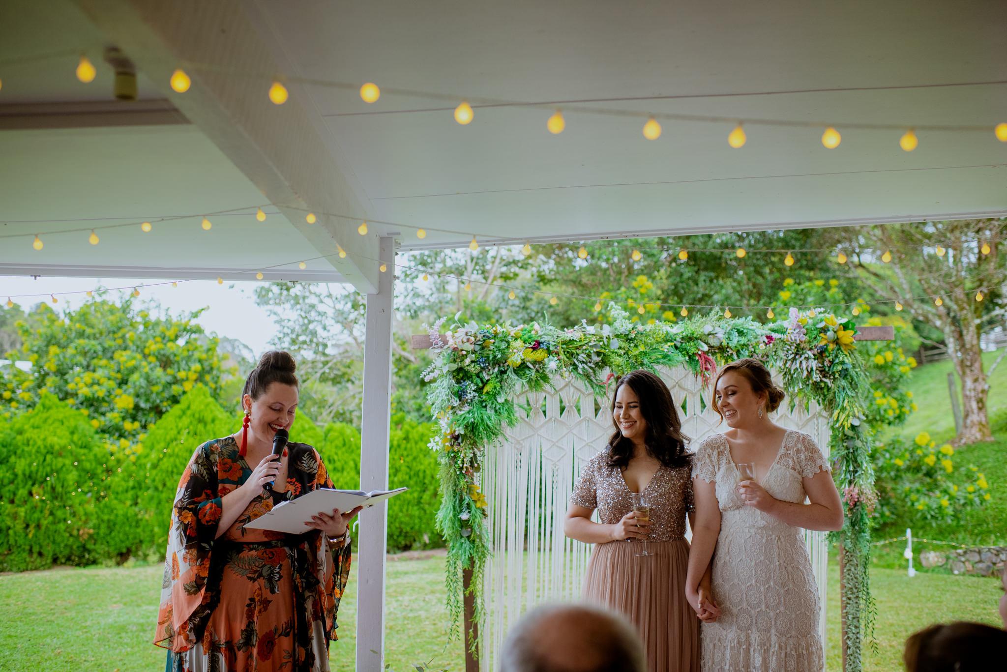Same sex backyard wedding ceremony with celebrant speaking in Maleny