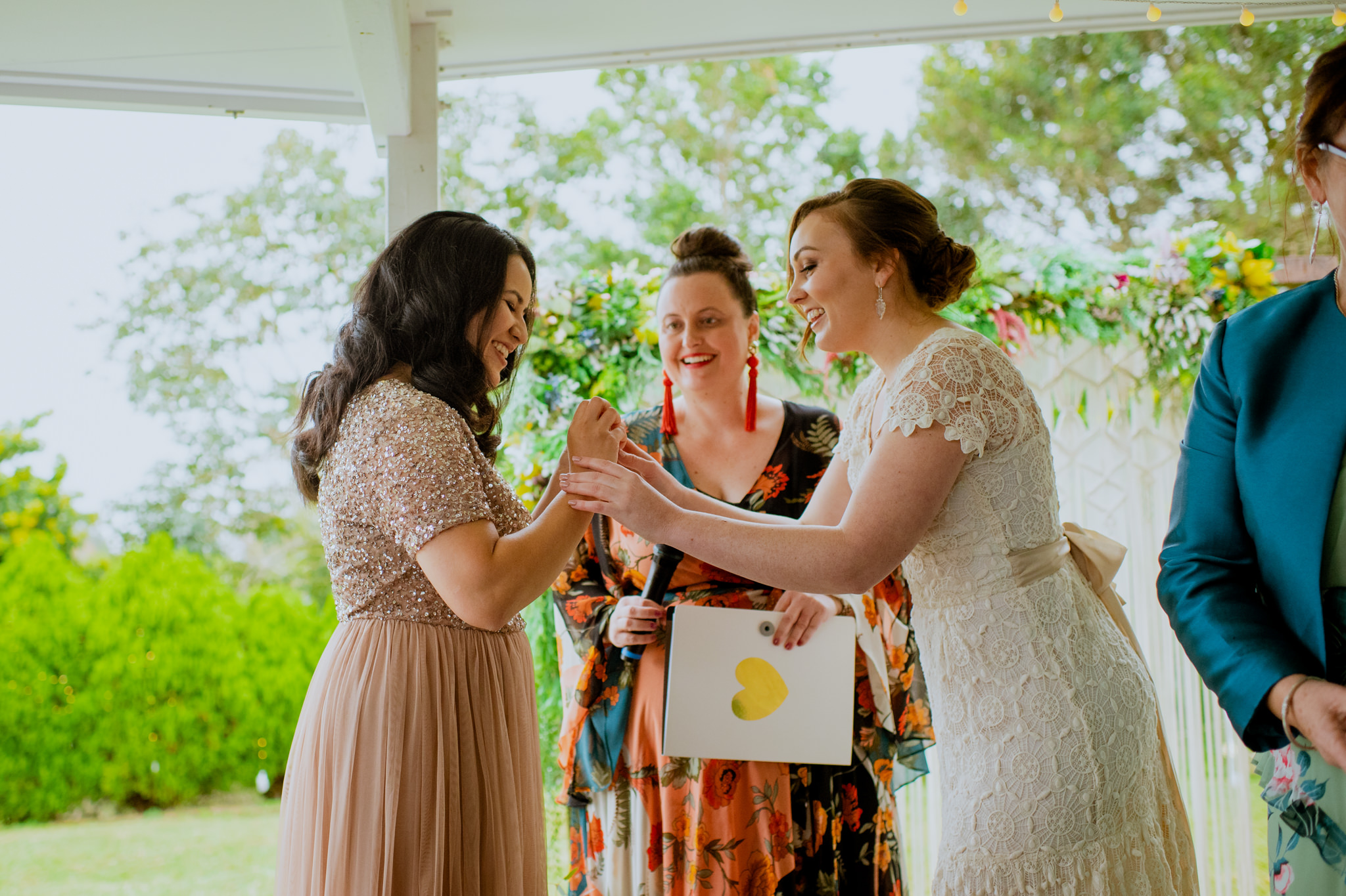 Same sex wedding ceremony with two brides playfully putting on rings