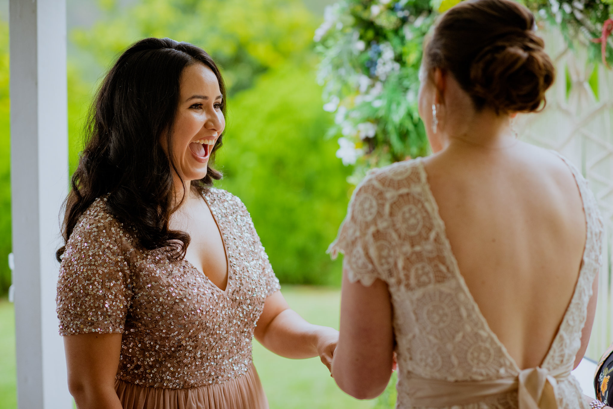 Happy bride laughs as her partner places ring on hand