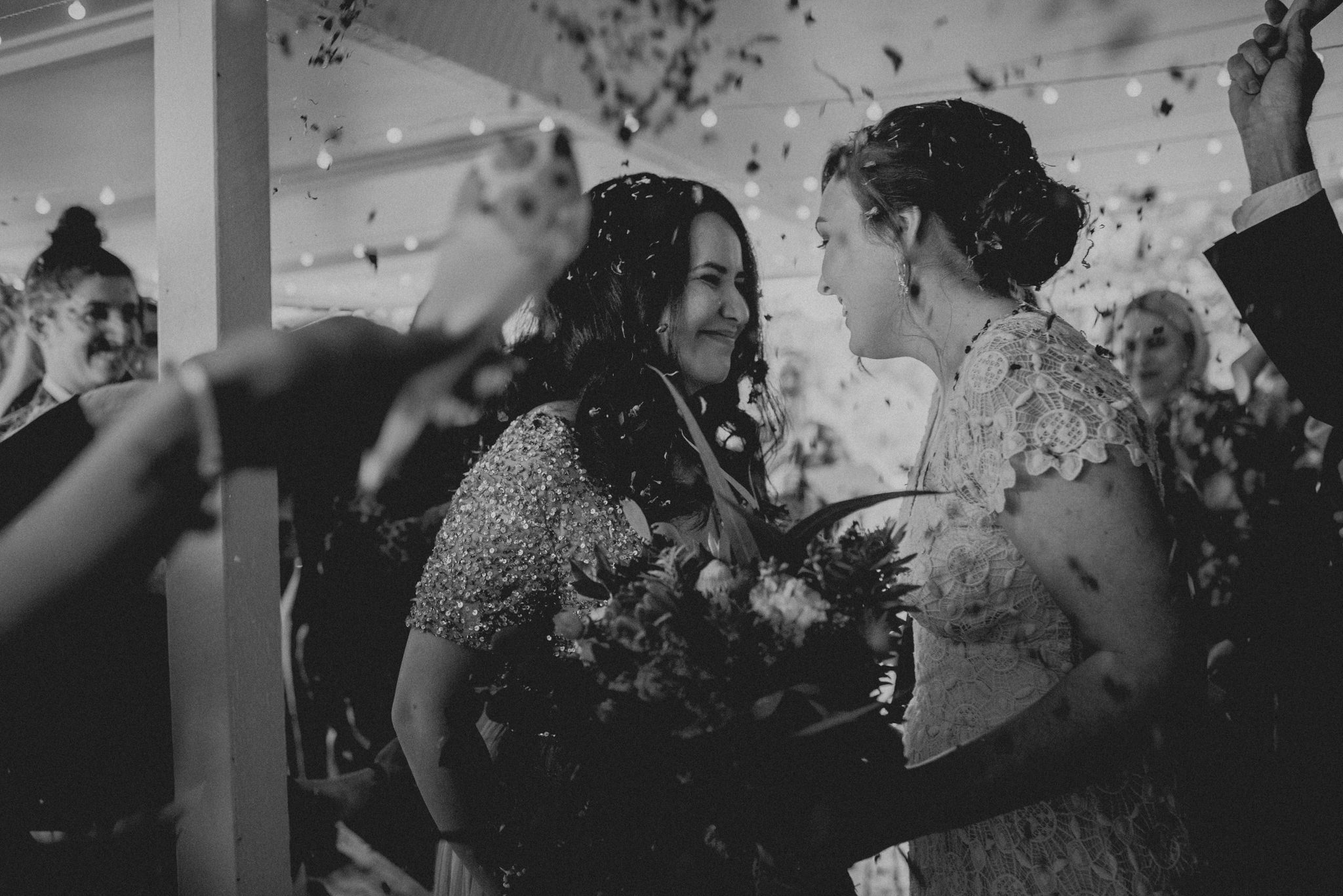 Brides laughing and smiling as hands throw flower petals on them