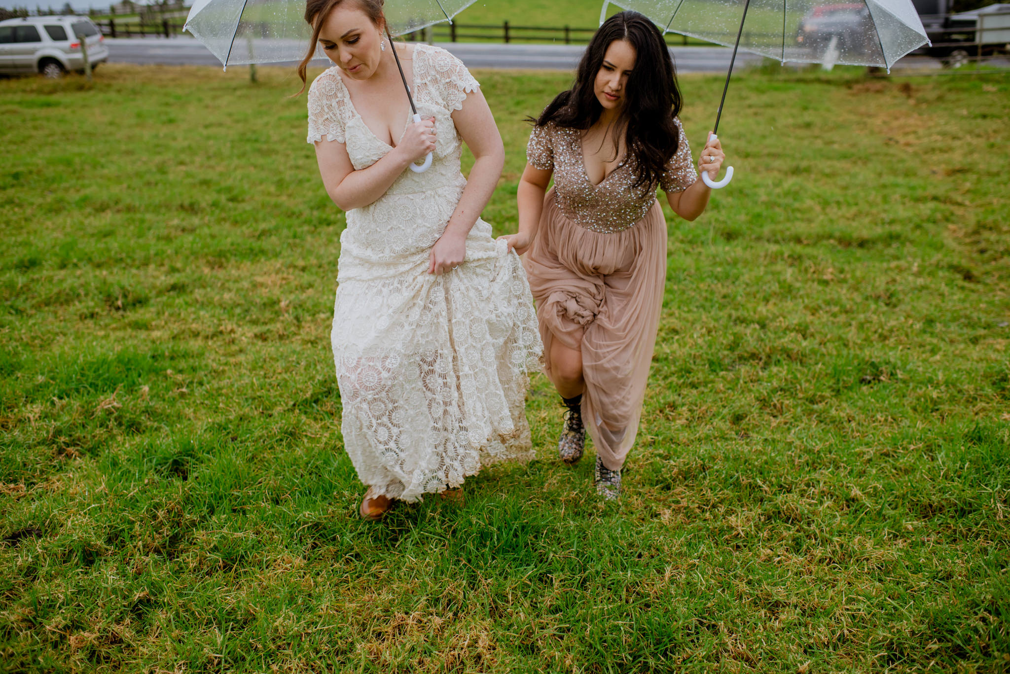 Two brides holding their dresses and umbrellas walking through wet grass in Maleny