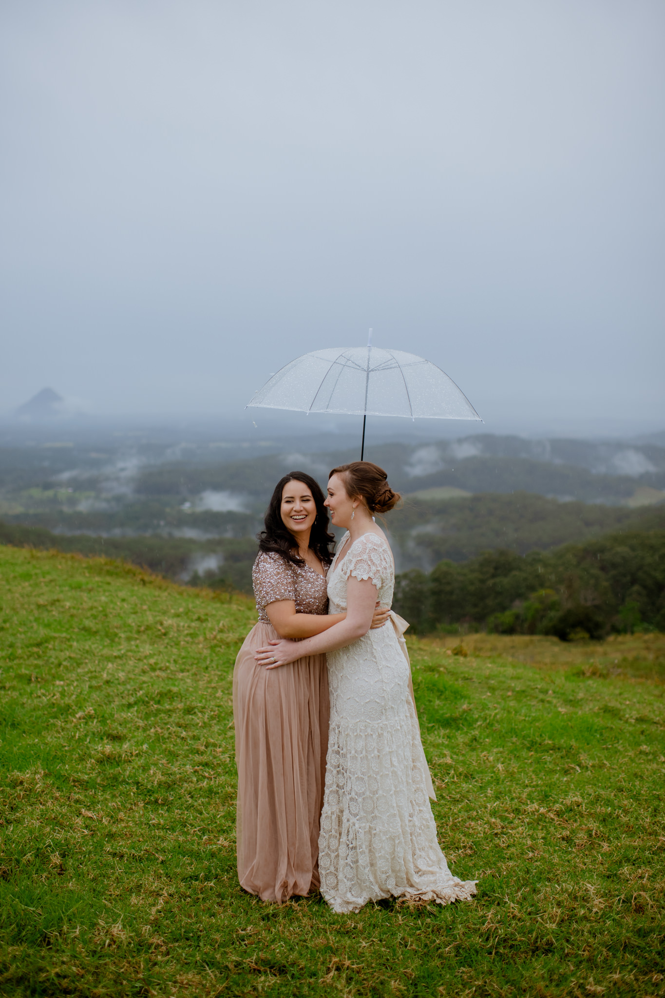 Two brides hugging underneath an umbrealla on a grassy hill in Maleny