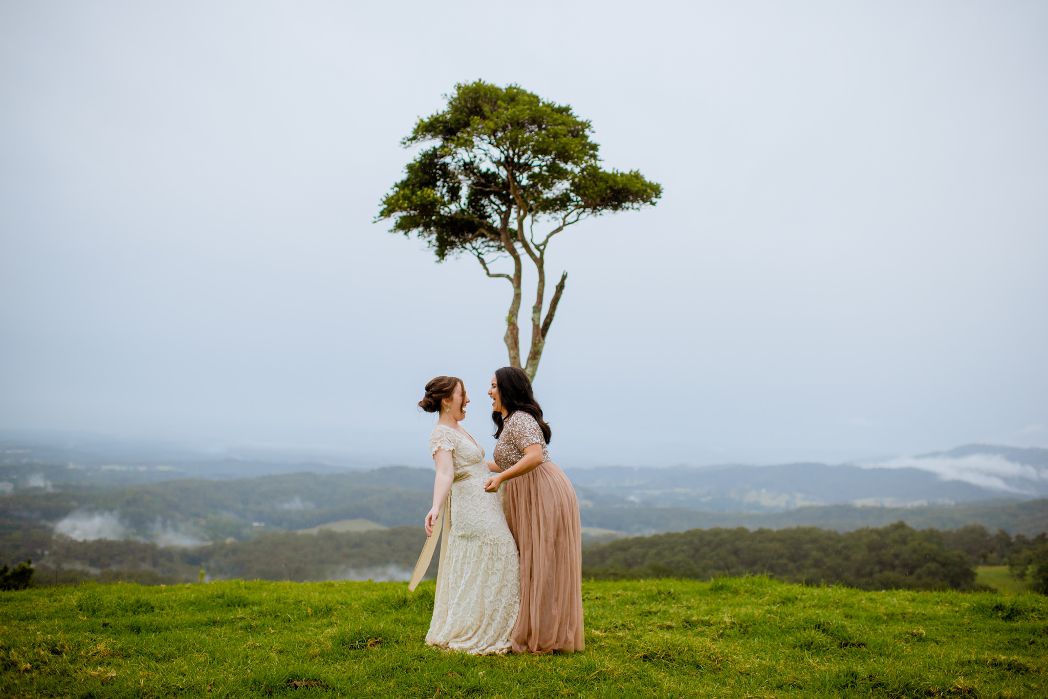 Two brides playfully dancing in front of a single tree on a grassy hill in Maleny