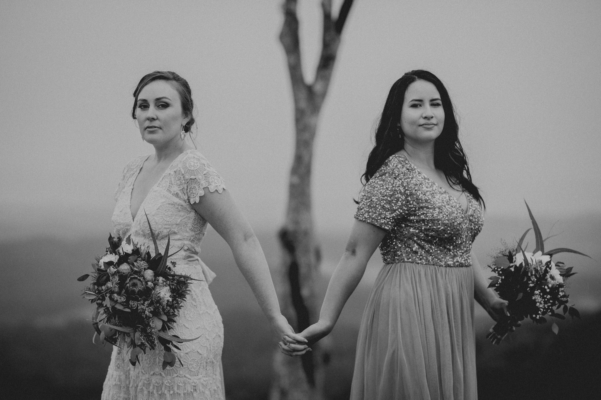 Two brides holding hands back to back looking serious at camera