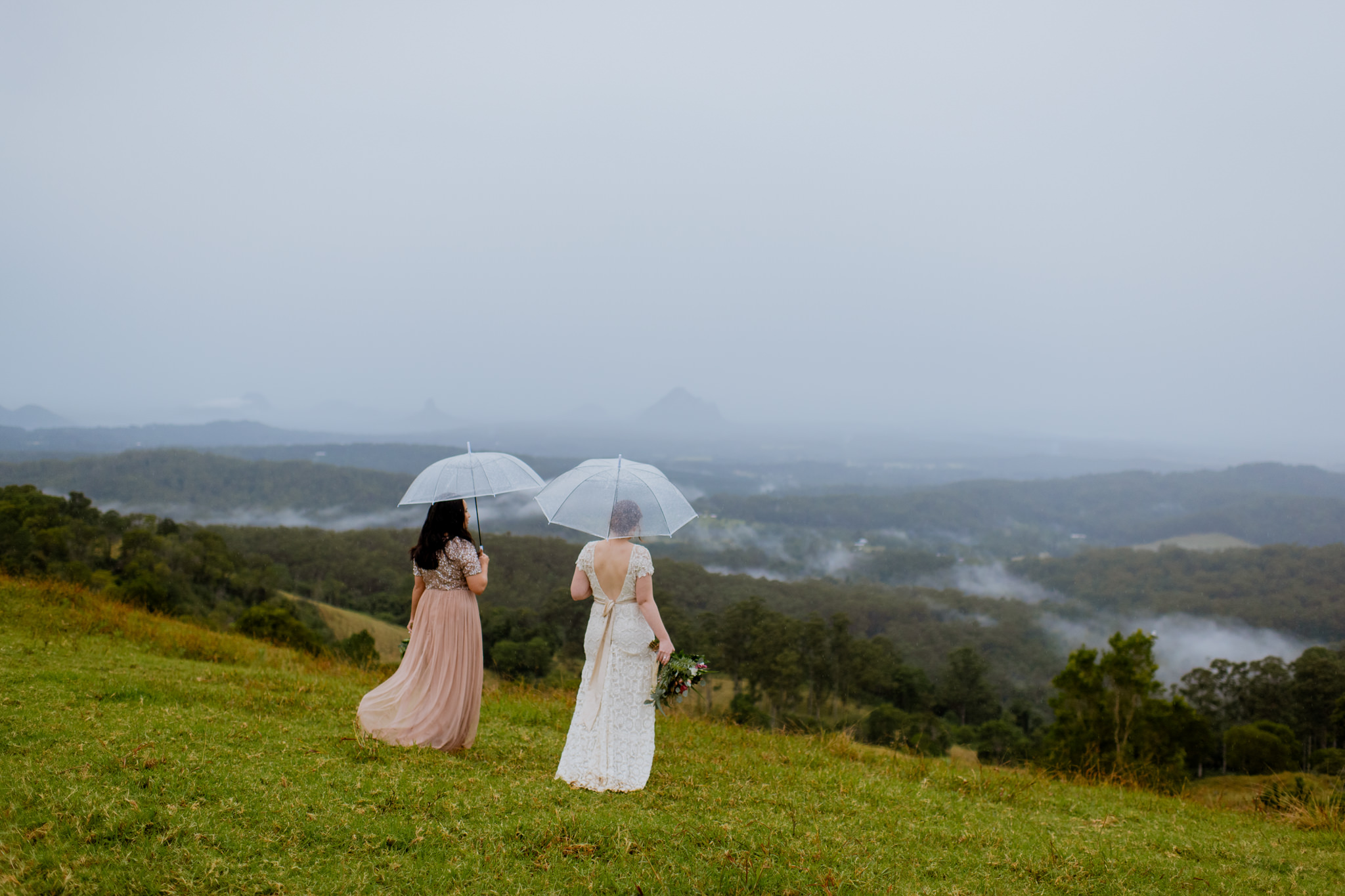 Same sex couple standing with umbrellas overlooking a cloudy Maleny valley