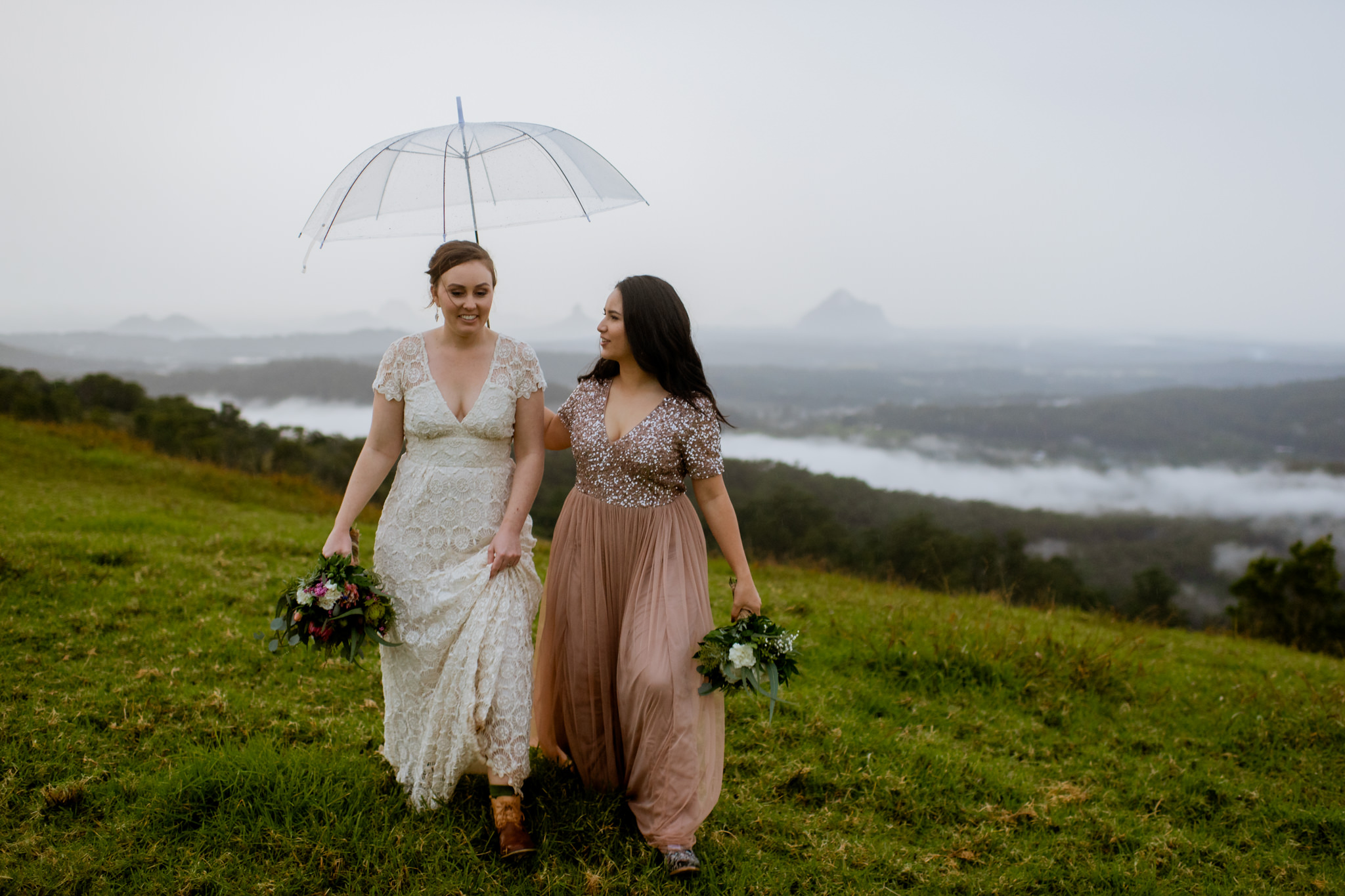 Same sex couple walk through a grassy hill overlooking a cloudy valley