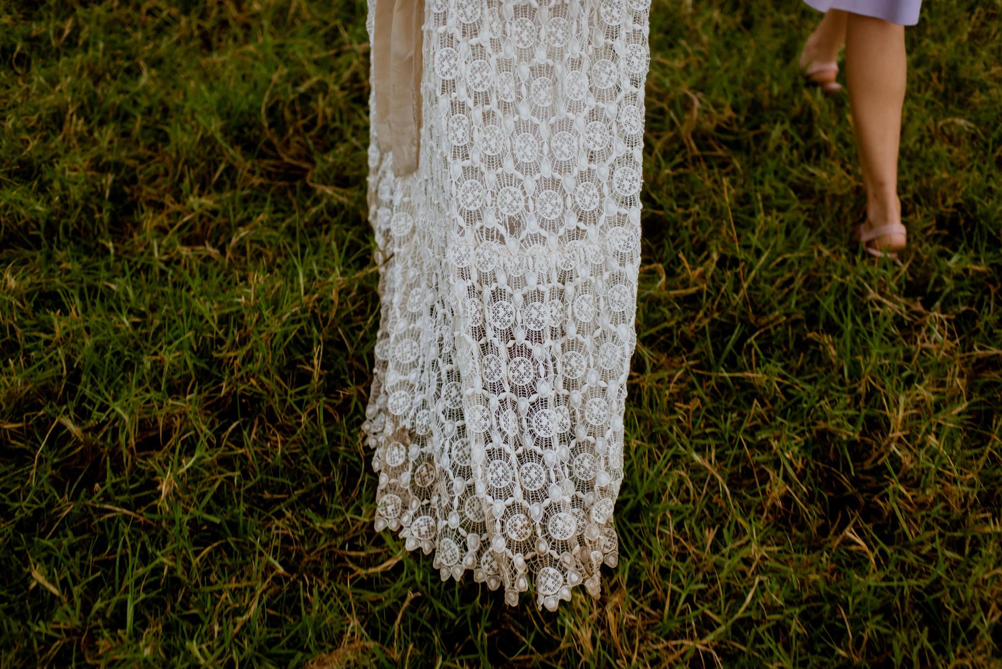 Close up of muddy wedding dress train on grass