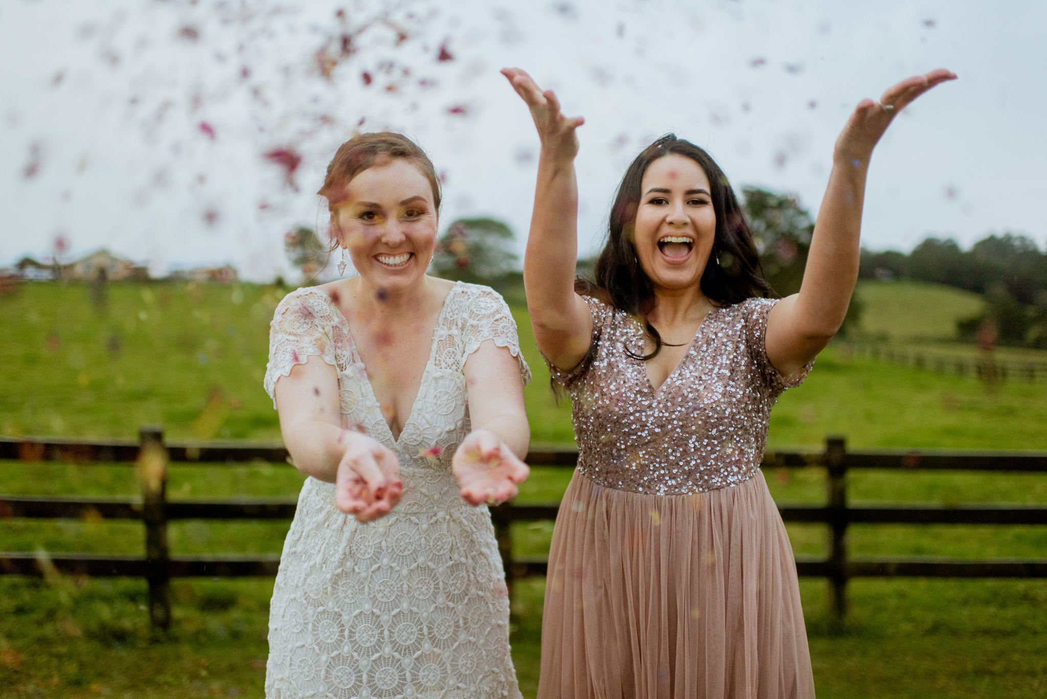 Lesbian couple playfully cheering and throwing confetti at camera