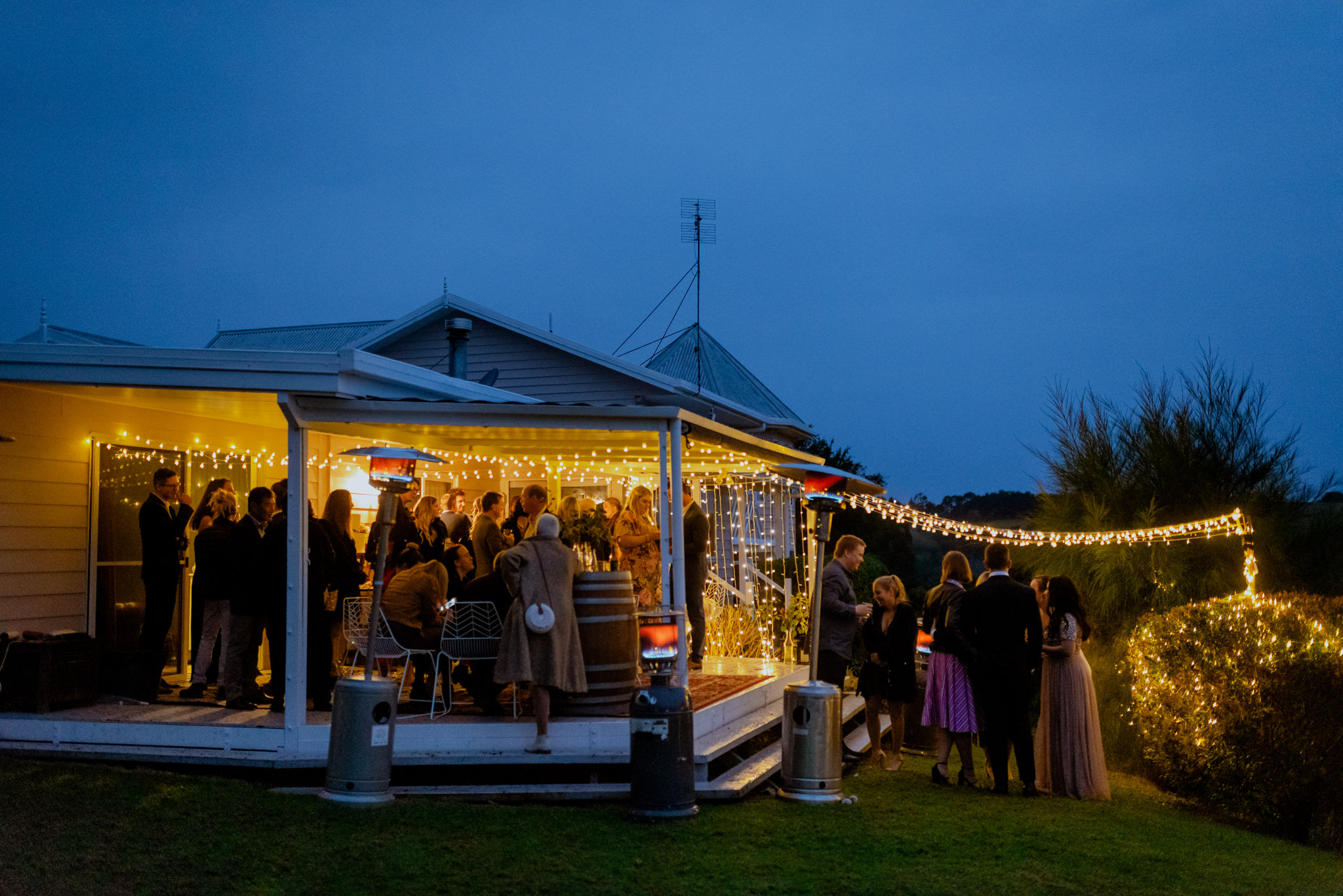 Party on a backyard verandah lit up by yellow fairy lights at dusk