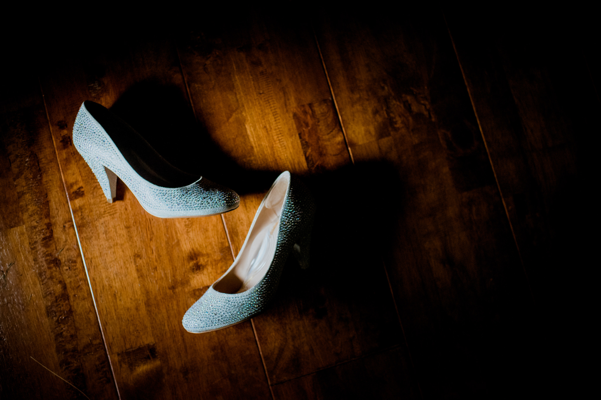 Sparkly wedding shoes lie on a wooden floor in a spot of soft light