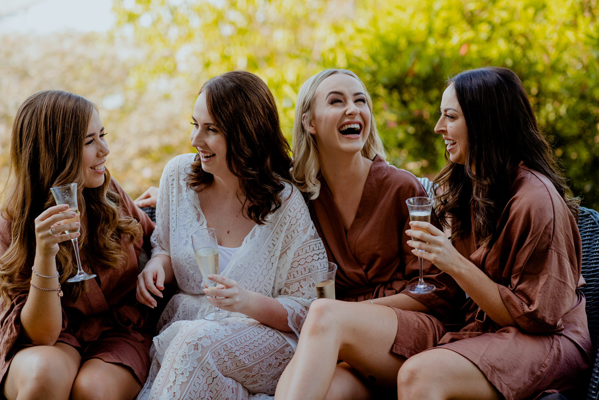 Four women in robes laugh together and drink champagne