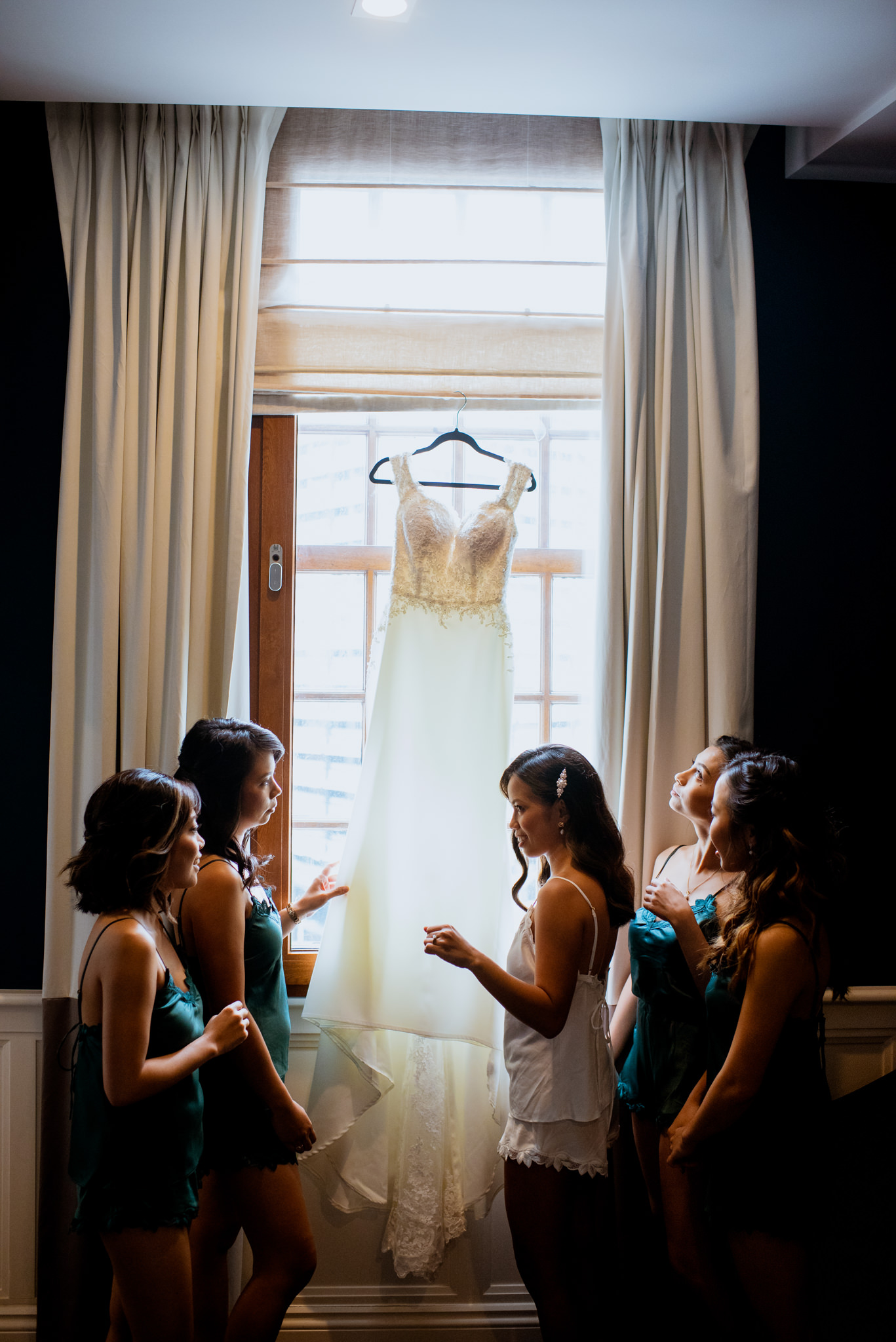 A bride and her four bridesmaids admire a wedding dress hanging in a window