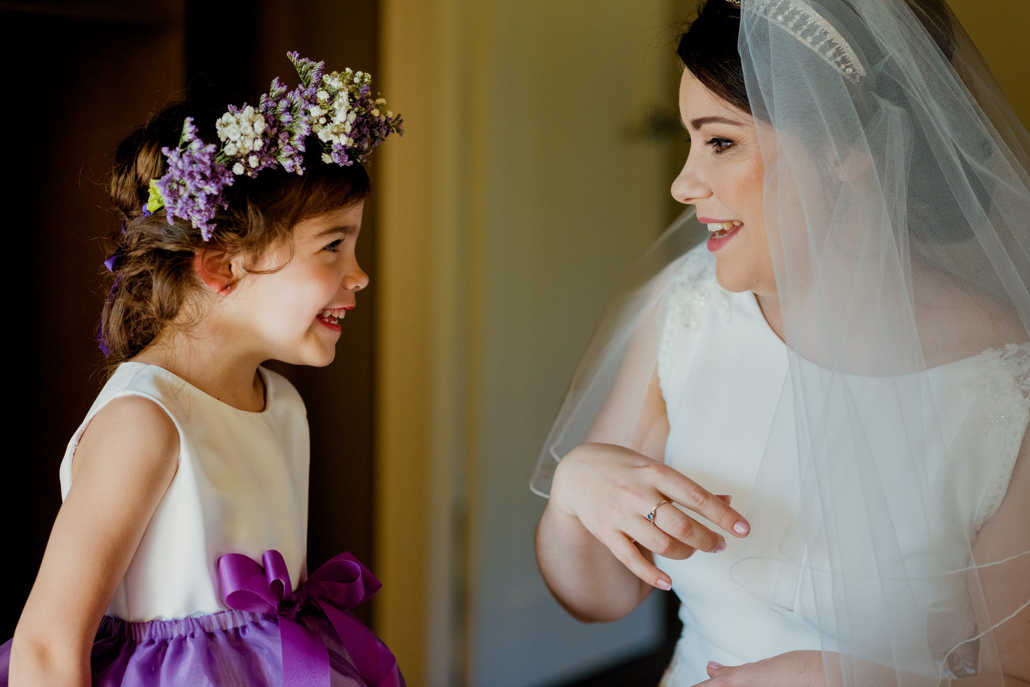 A smiling bride laughs with a young flowergirl
