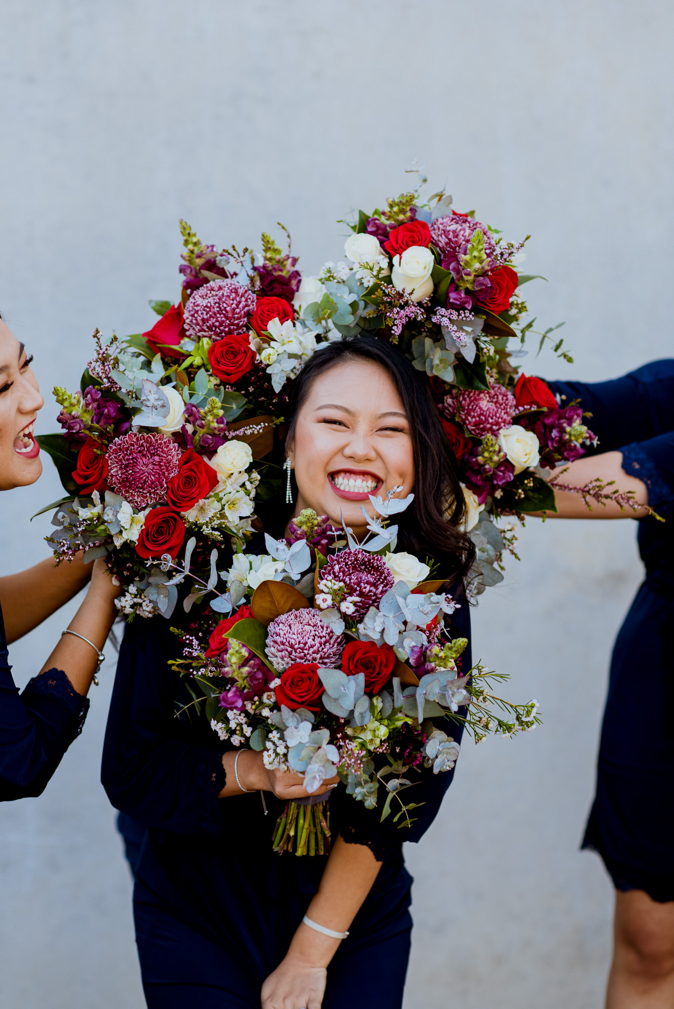 An asian girl smiles as her face is surrounded by wedding bouquets