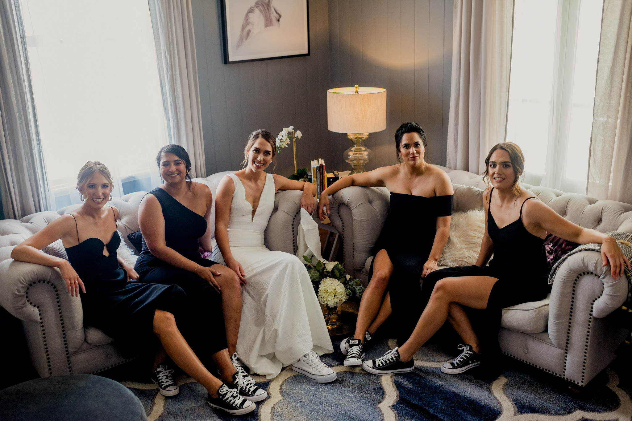 A bride and her bridesmaids sit on lounges and show off their sneakers